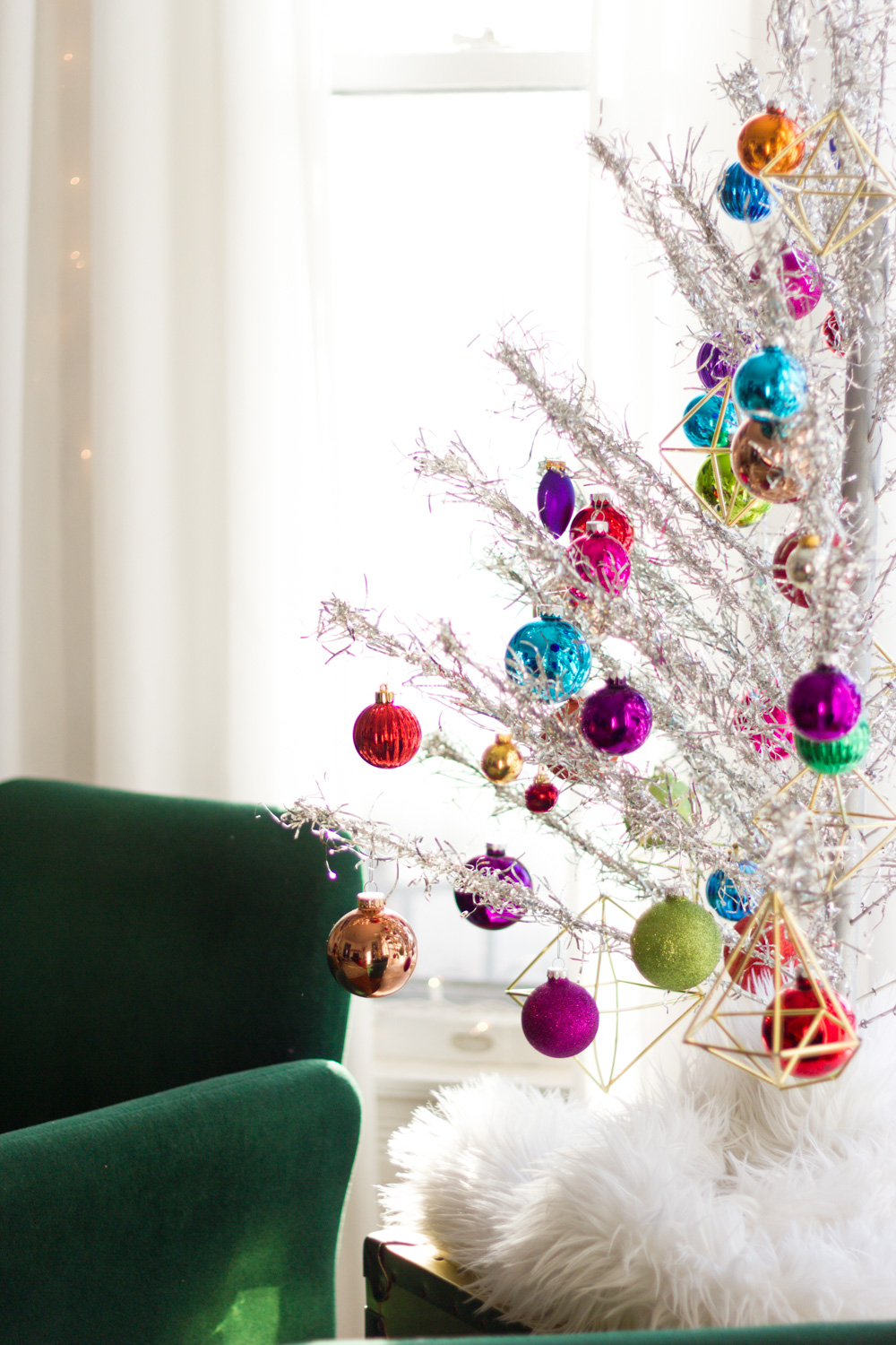 vintage silver aluminum Christmas tree with colorful ornaments, green velvet chair