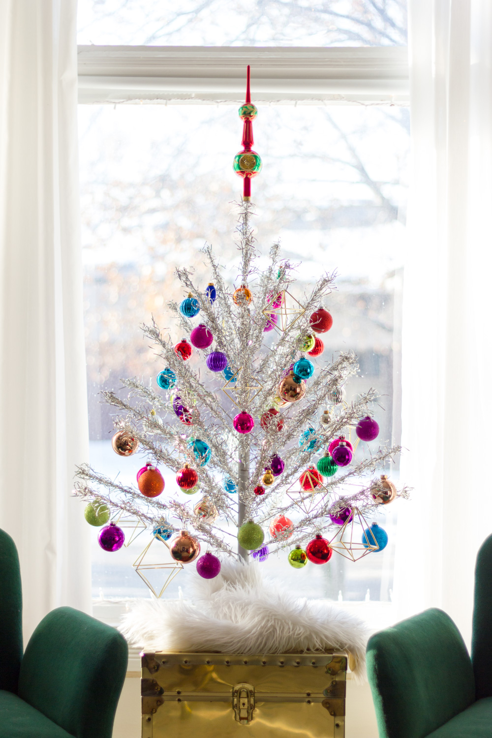 vintage silver aluminum Christmas tree with colorful ornaments, brass trunk, and green velvet chairs