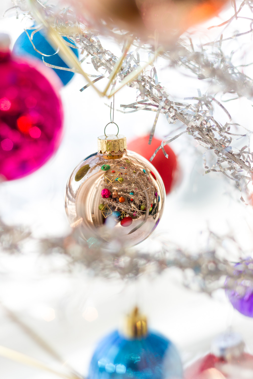 colorful ornaments on vintage silver aluminum Christmas tree