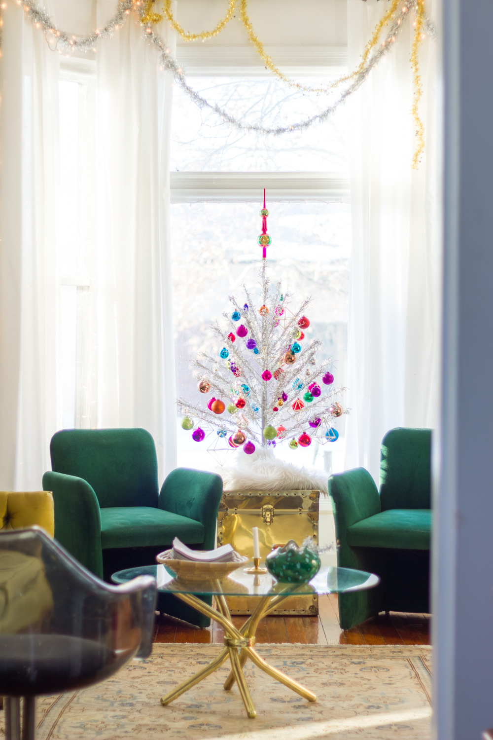 living room with vintage colorful silver aluminum Christmas tree, brass trunk, and green velvet chairs