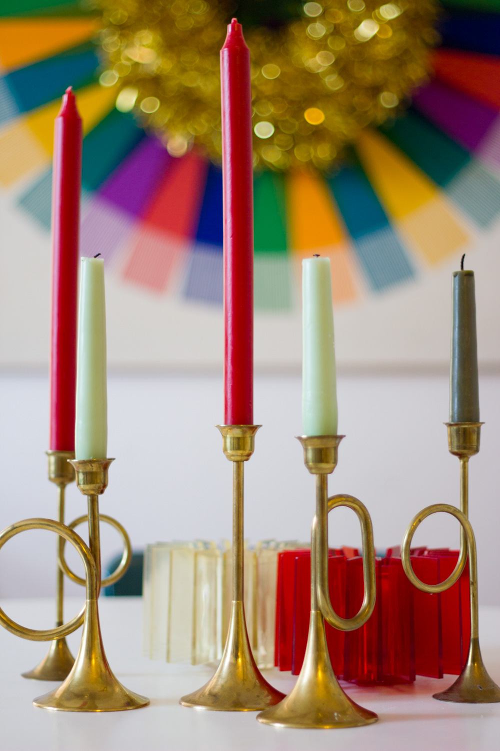 red and green taper candles in brass Christmas candleholders