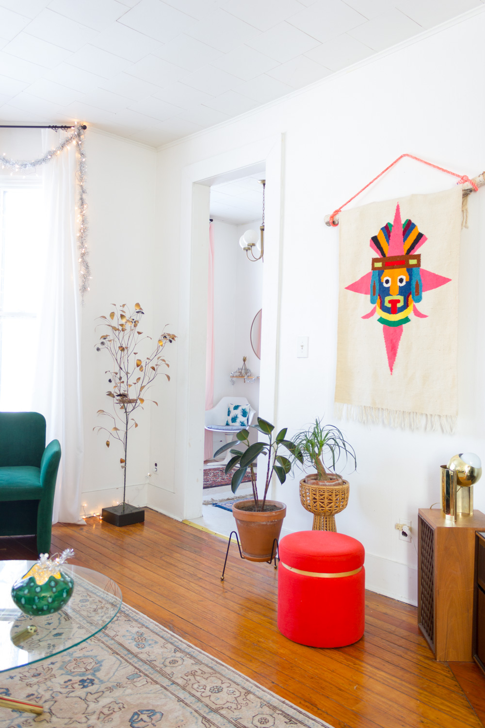 living room with colorful vintage wall hanging