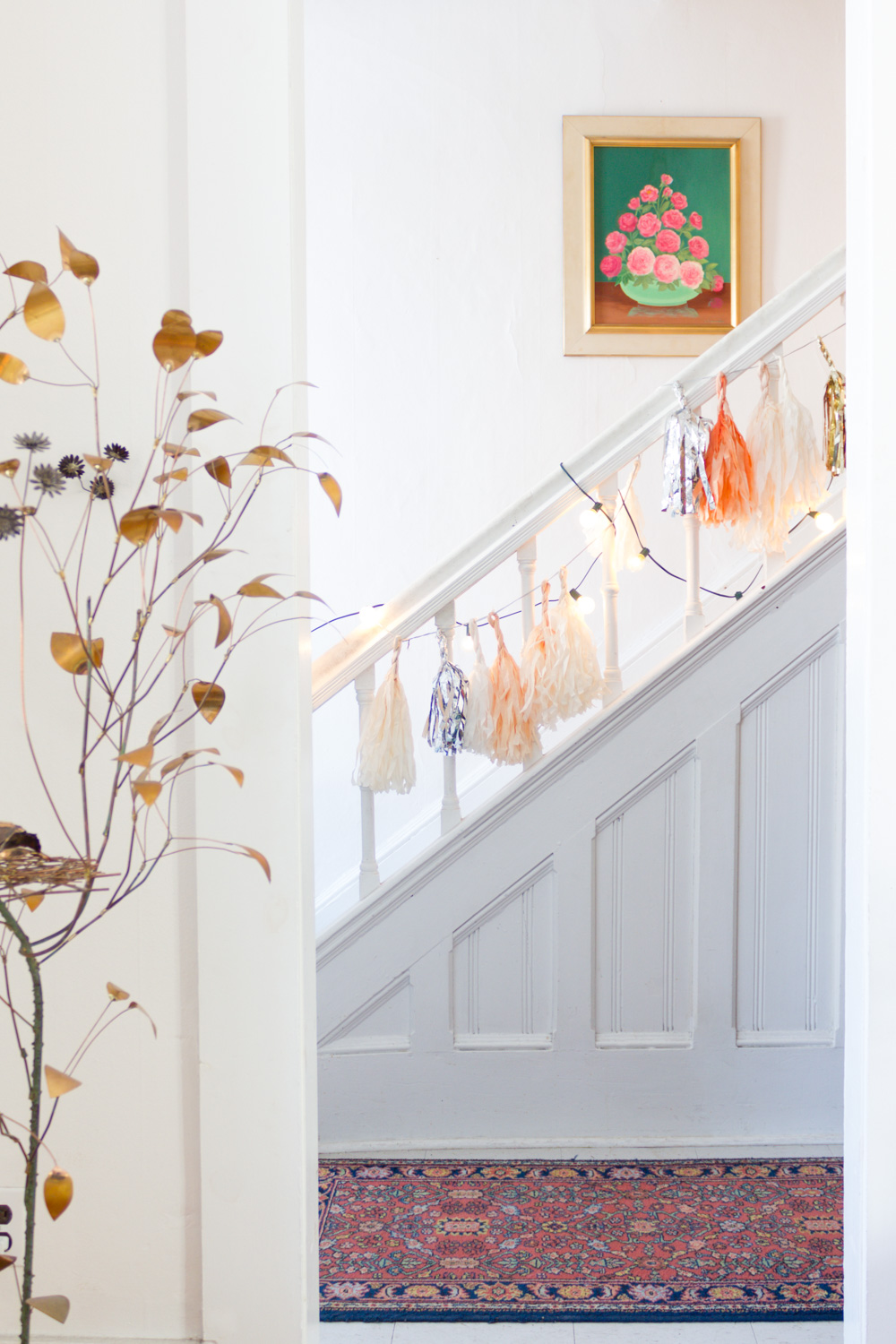 metallic garland and string lights on stairwell in entryway