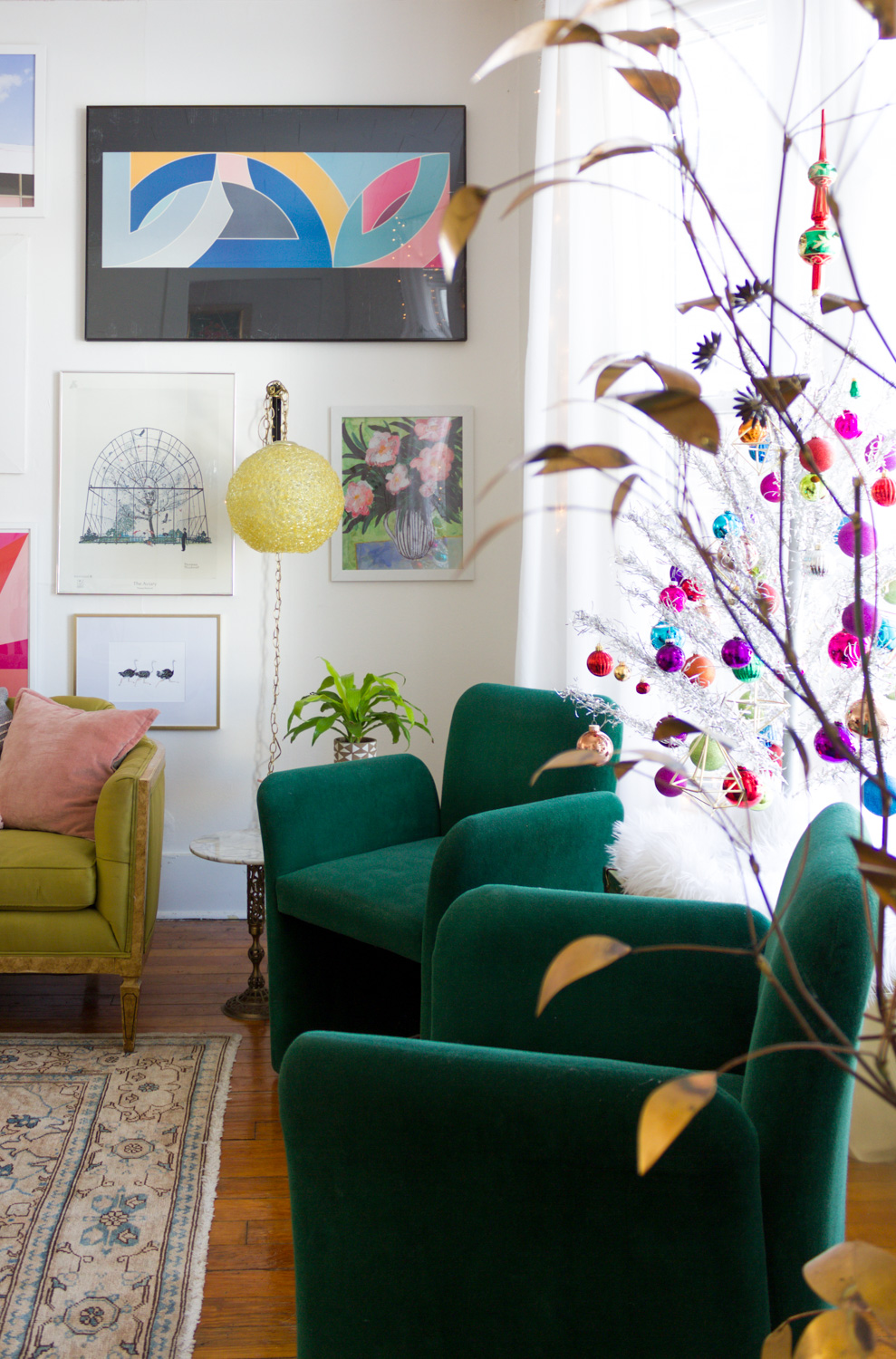 living room gallery wall with green velvet chairs and vintage silver aluminum Christmas tree