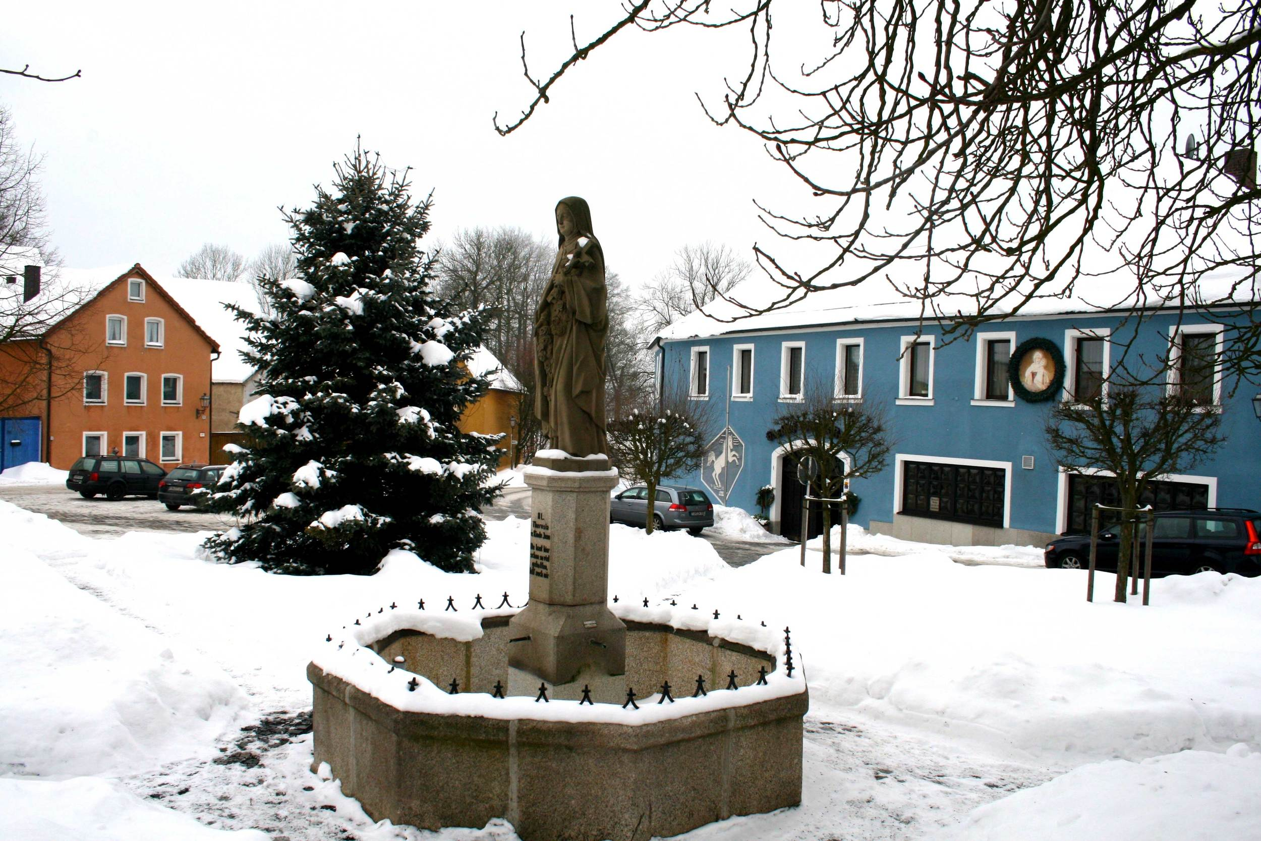 Image©sourcingstyle.com, statue of Little Flower, Saint Therese of Lisieux at Konnersreuth facing the house of Saint Therese Neumann (the house is not visible in the picture. The blue house is the hotel Weisses Ross, where I stayed during my stay.)