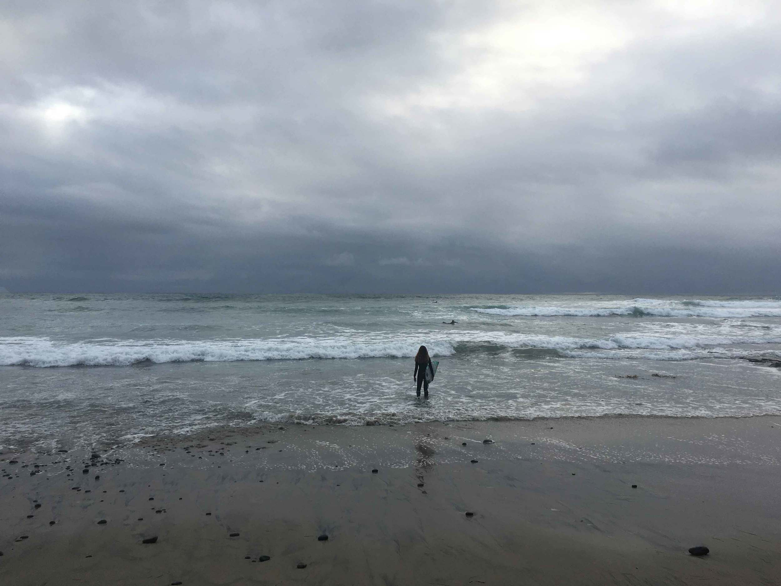 Surfer standing in the ocean, surfer with surfboard, stormy day at the ocean, Swamis beach, Encinitas, California. Image©sourcingstyle.com