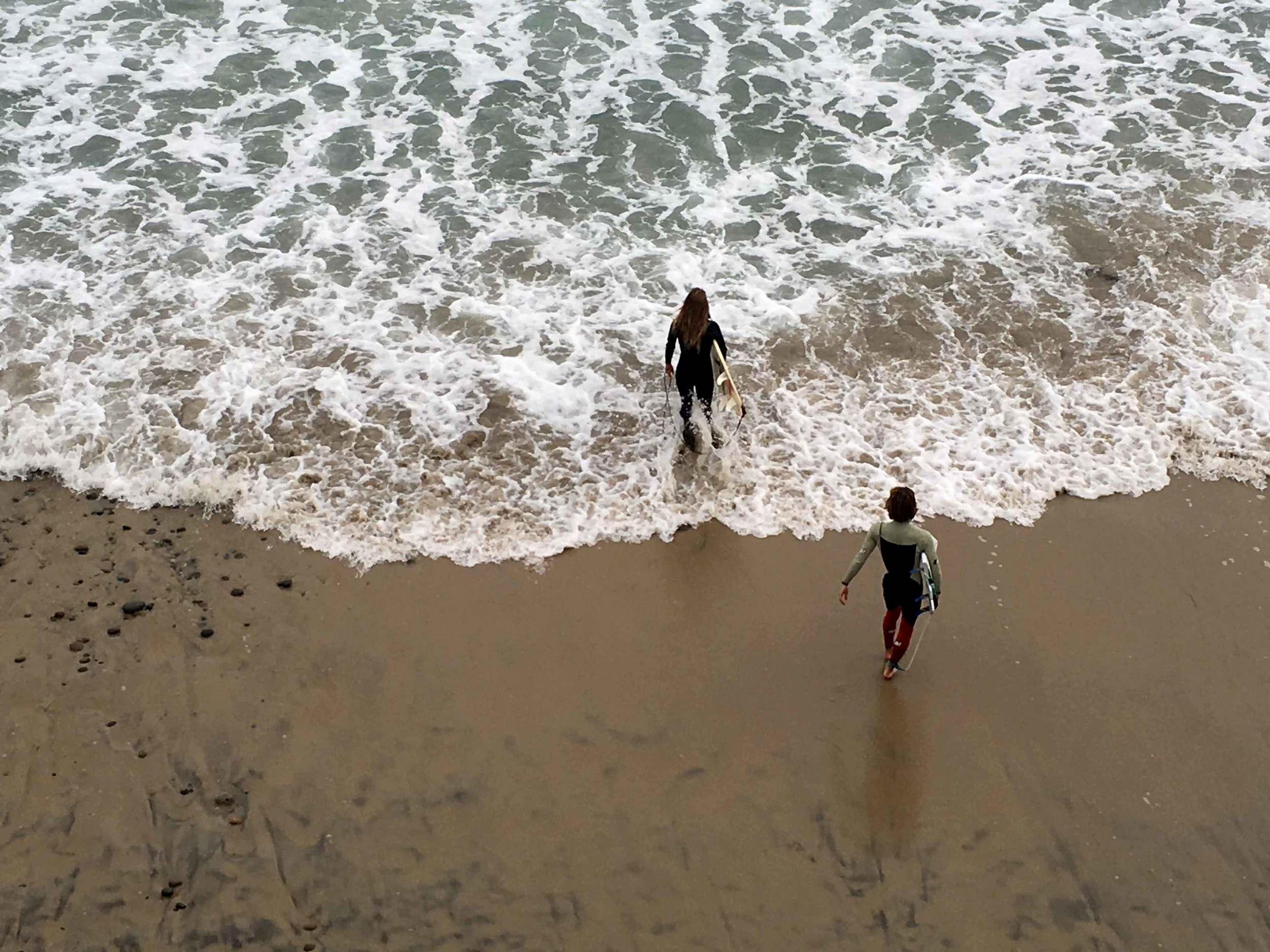 Surfers walking into the ocean, Swamis beach, Encinitas, California. Image©sourcingstyle.com