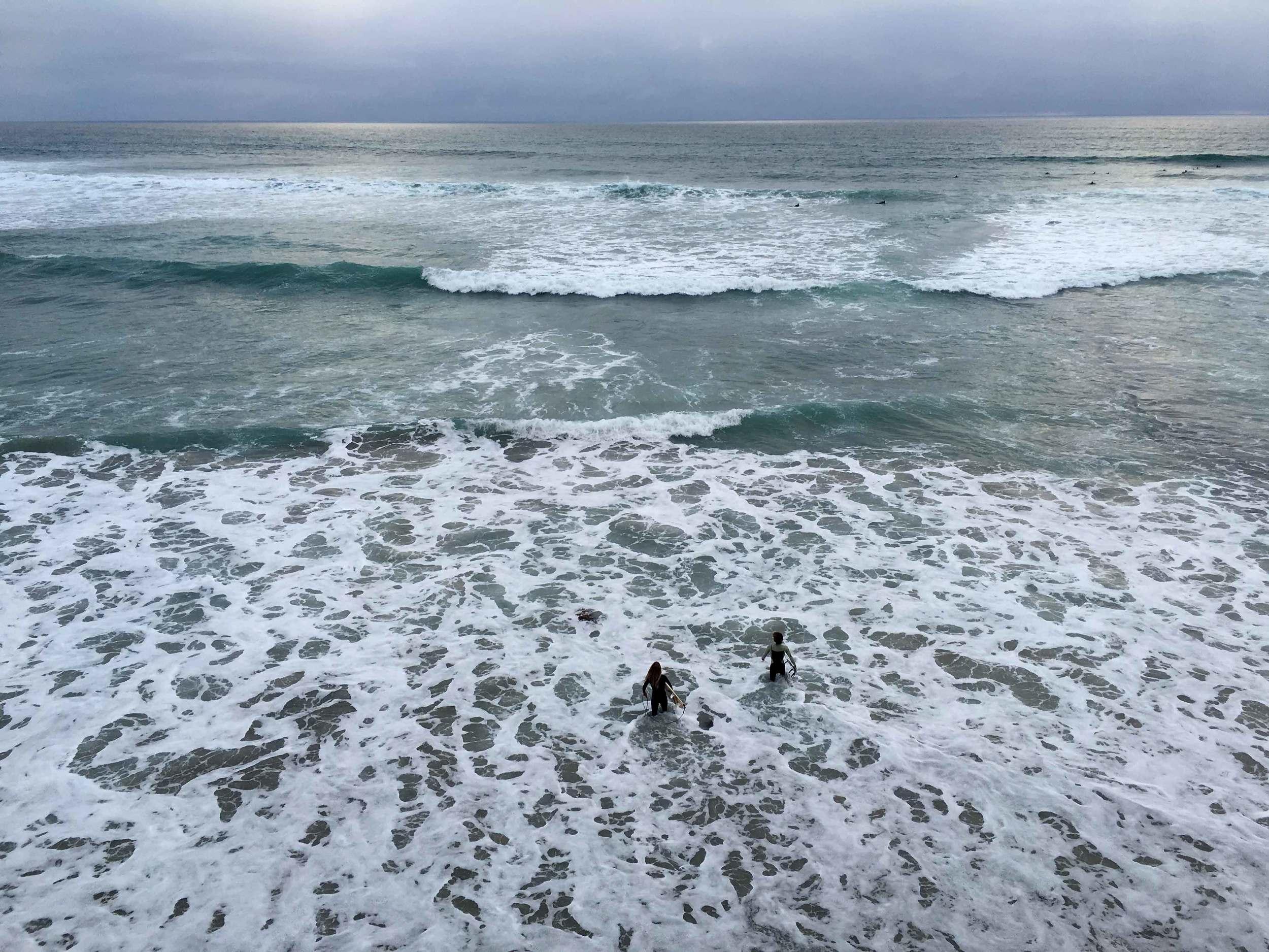 Surfers walking into the ocean, storm at the ocean, ocean view, Swamis beach, Encinitas, California. Image©sourcingstyle.com