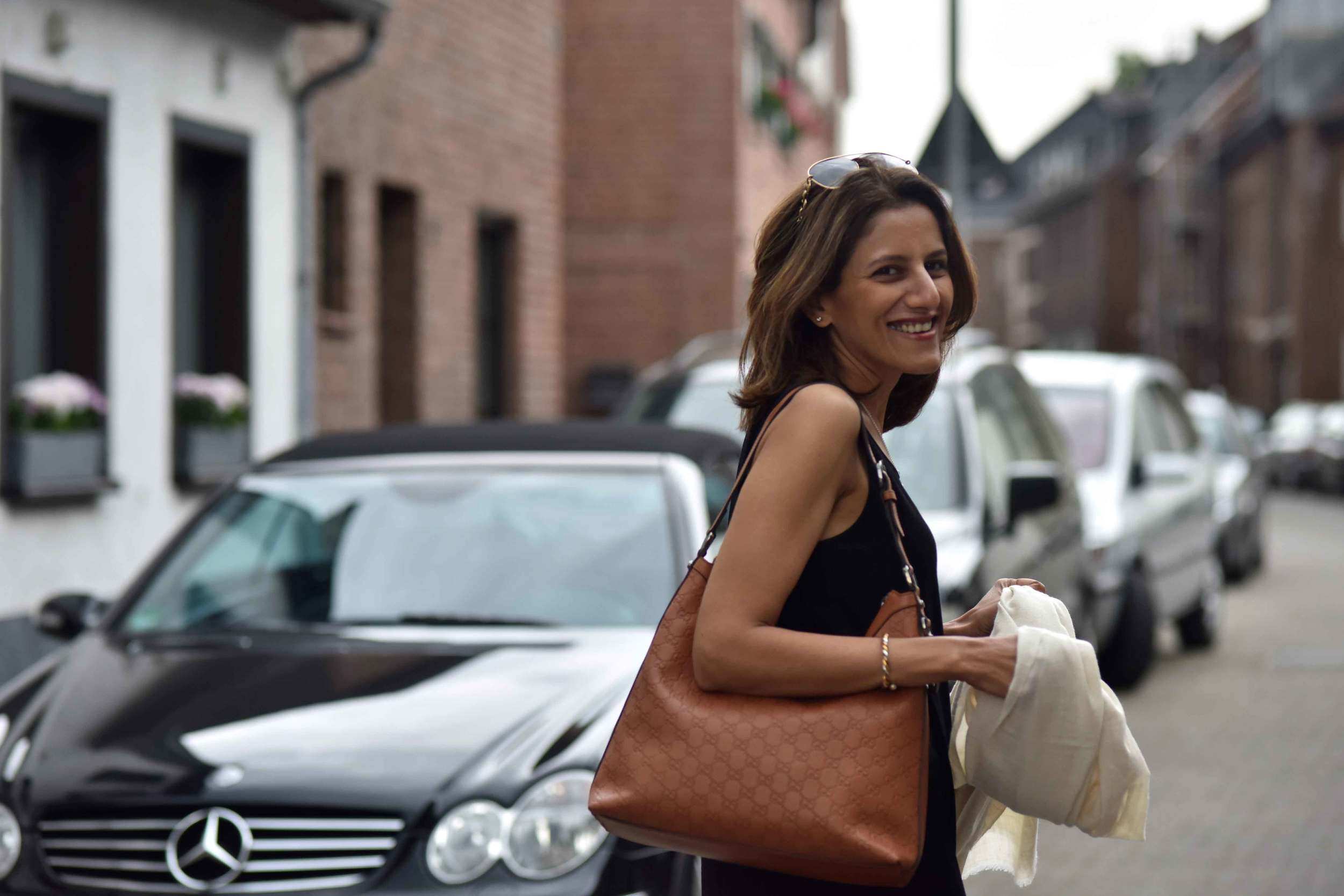 Ready to step out, wearing Eileen Fisher black tank dress in viscose jersey, little black dress, Gucci handbag. Image©sourcingstyle.com, Photo: Nicola Nolting.