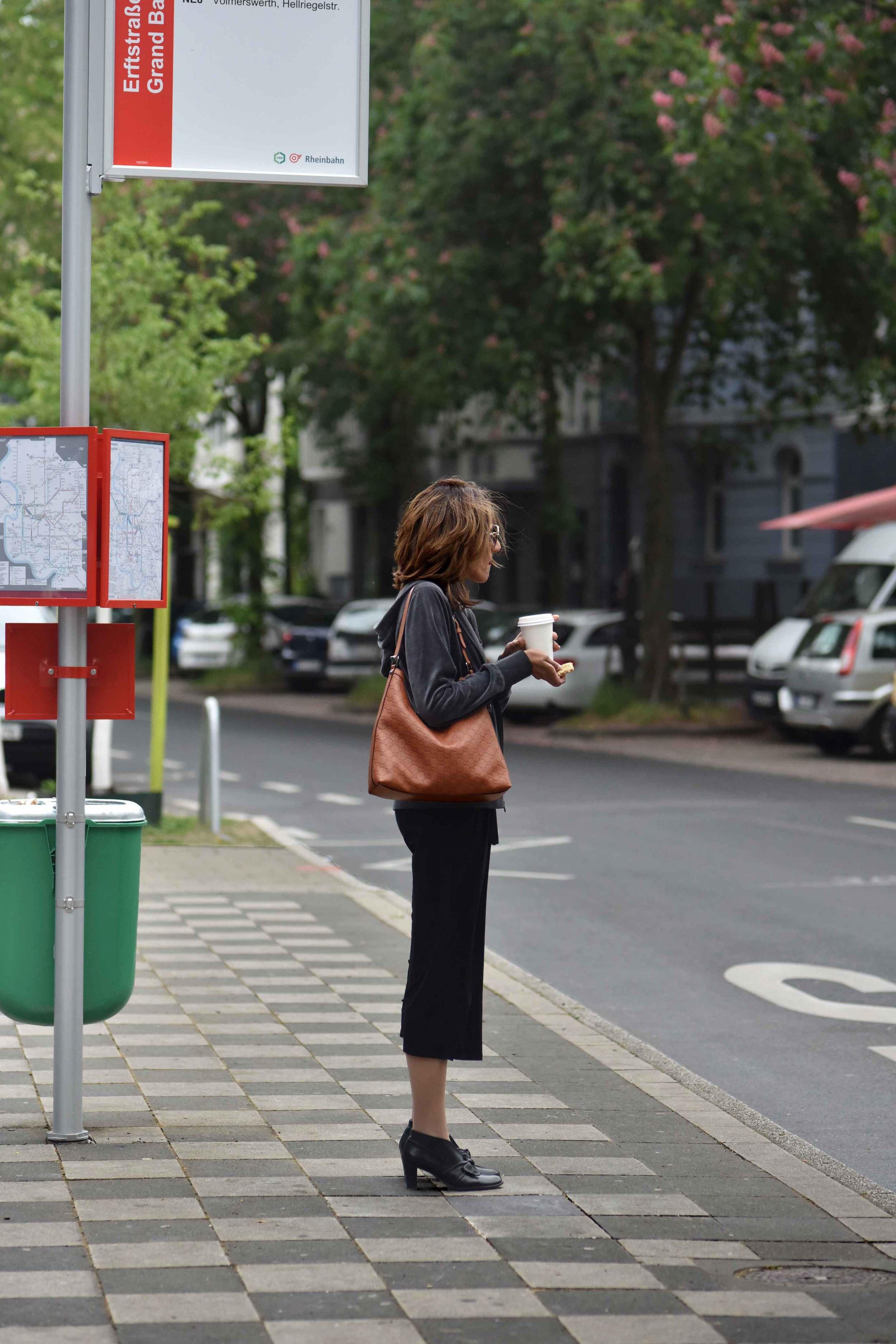 At the bus stop. Wearing Eileen Fisher black tank dress in viscose jersey, little black dress, Gucci handbag, Eddie Bauer velour jacket, Düsseldorf city, Germany. Image©sourcingstyle.com, Photo: Nicola Nolting.