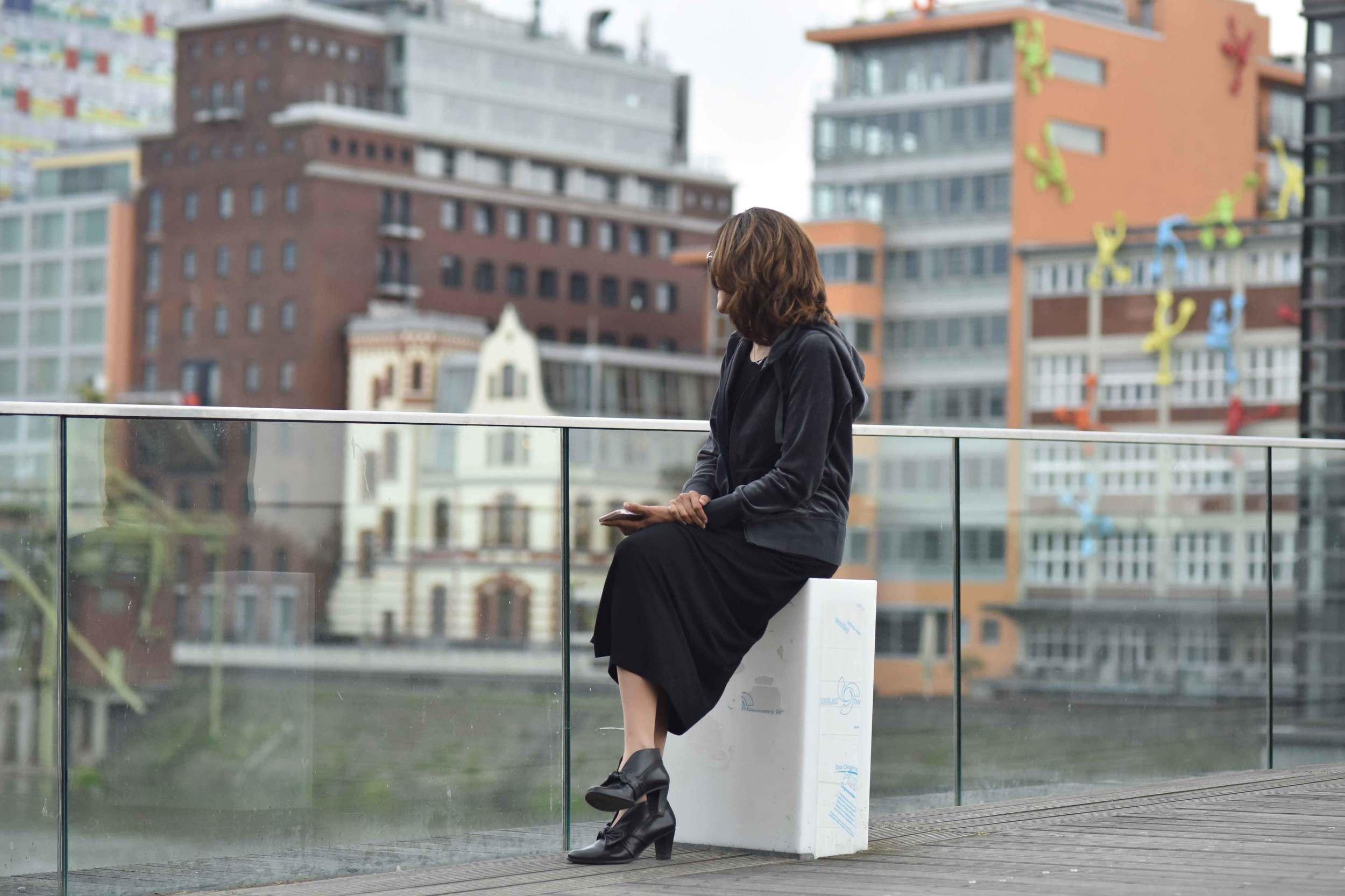 Wearing Eileen Fisher black tank dress in viscose jersey, little black dress, Gucci handbag, Eddie Bauer velour jacket, Düsseldorf harbor, Germany. Image©sourcingstyle.com, Photo: Nicola Nolting.
