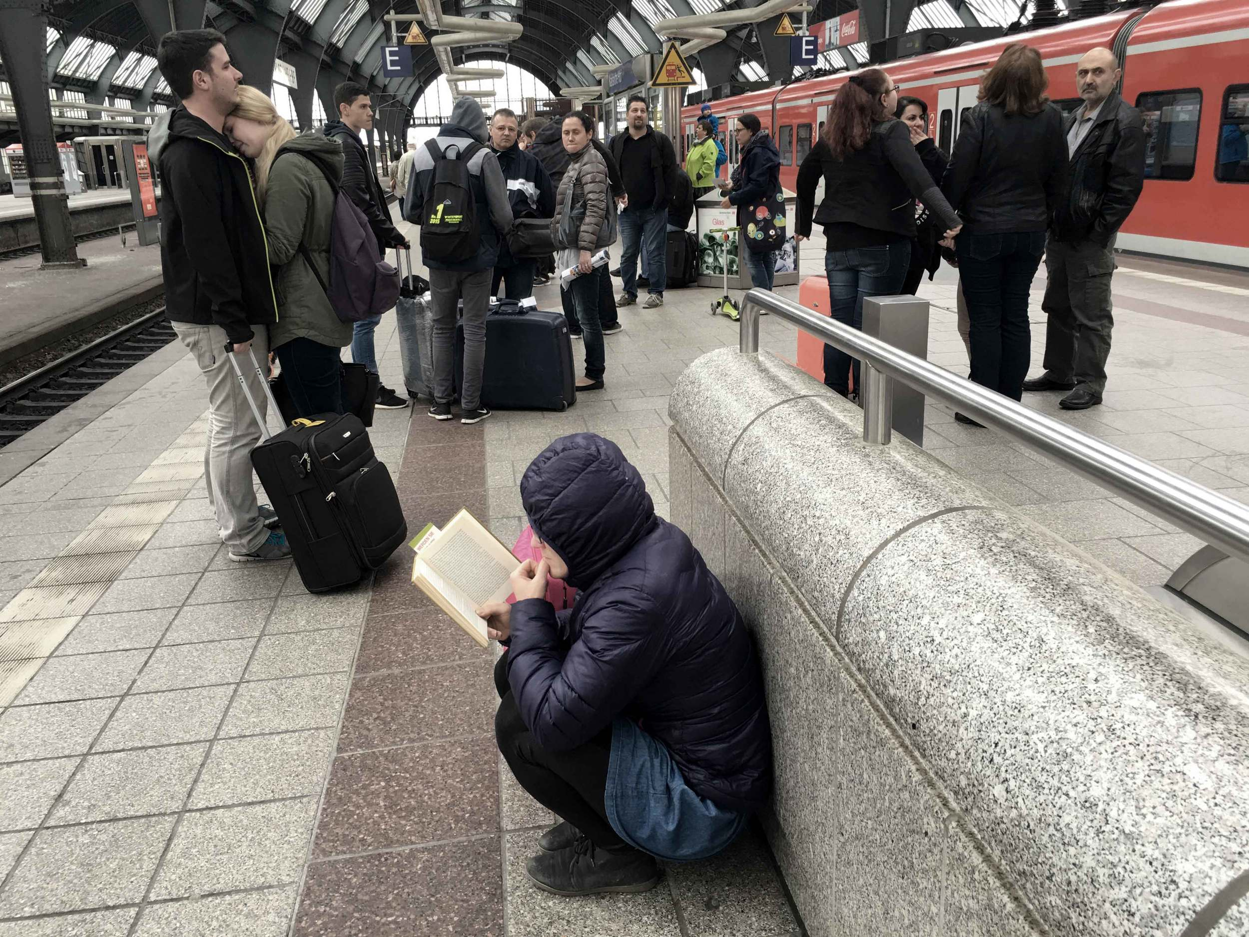 A platform in Germany, Karlsruhe railway station, girl reading a book on the platform, a couple hug and say goodby on the platform. Image©sourcingstyle.com