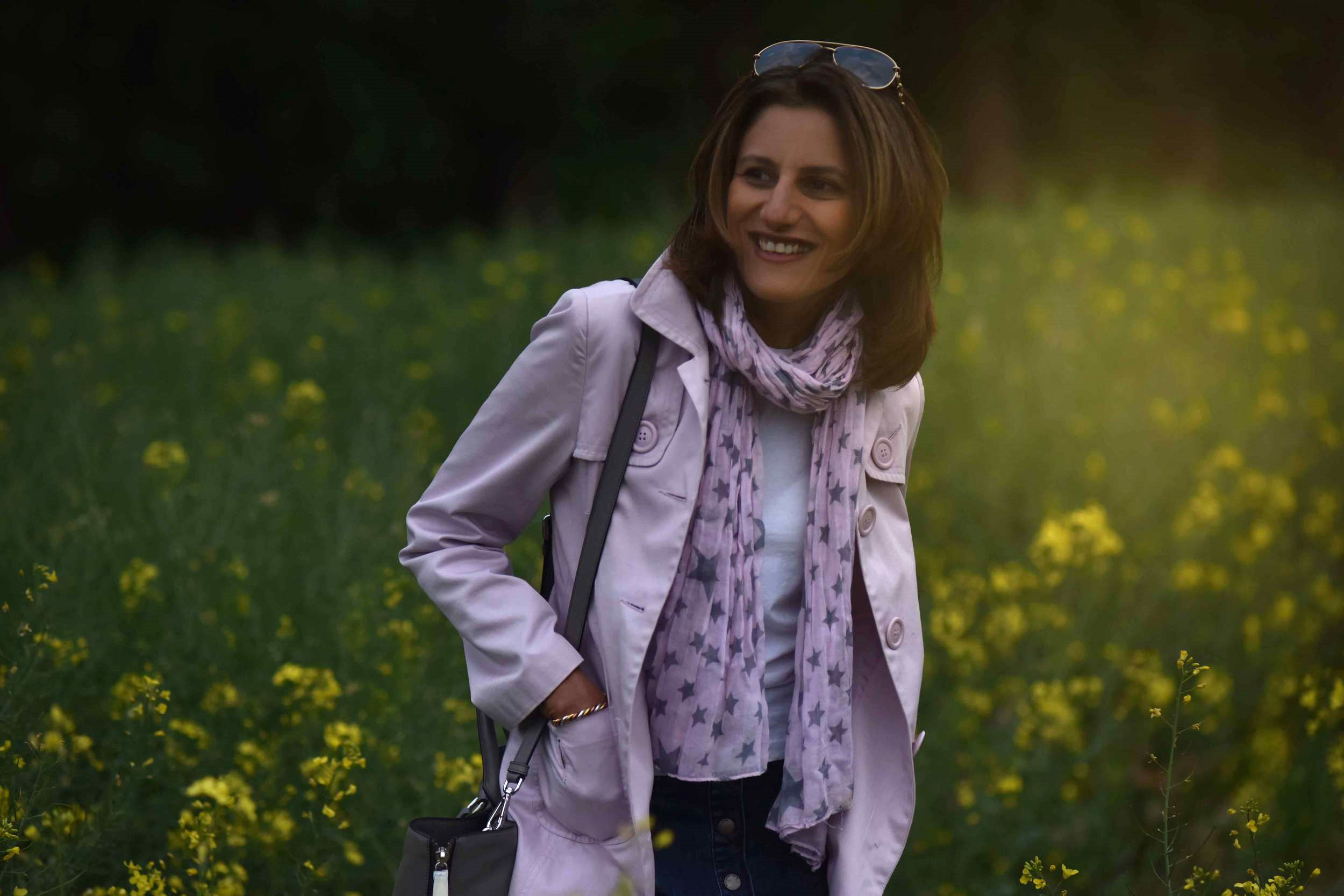 In the fields with flowers, village near Düsseldorf, Germany, pink trench, Ralph Lauren white tee, star scarf, Prada tote, Gucci sunglasses. Photo: Nicola Nolting, Image©sourcingstyle.com
