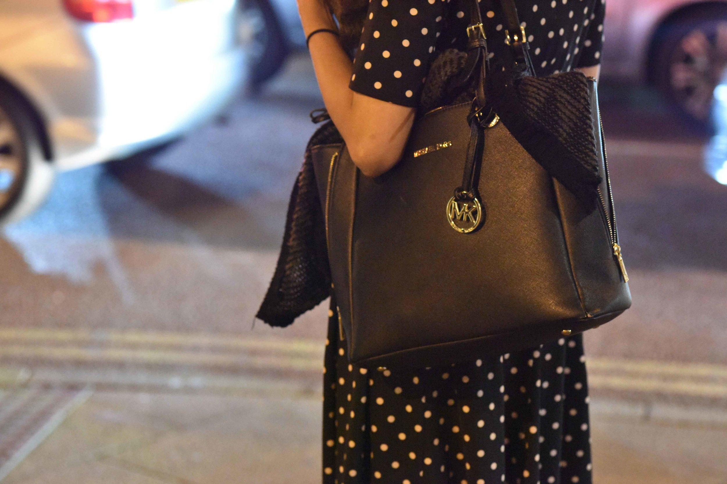 Michael Kors saffiano leather black tote, clicked at Wembley Park underground station, London, U.K. Image©sourcingstyle.com