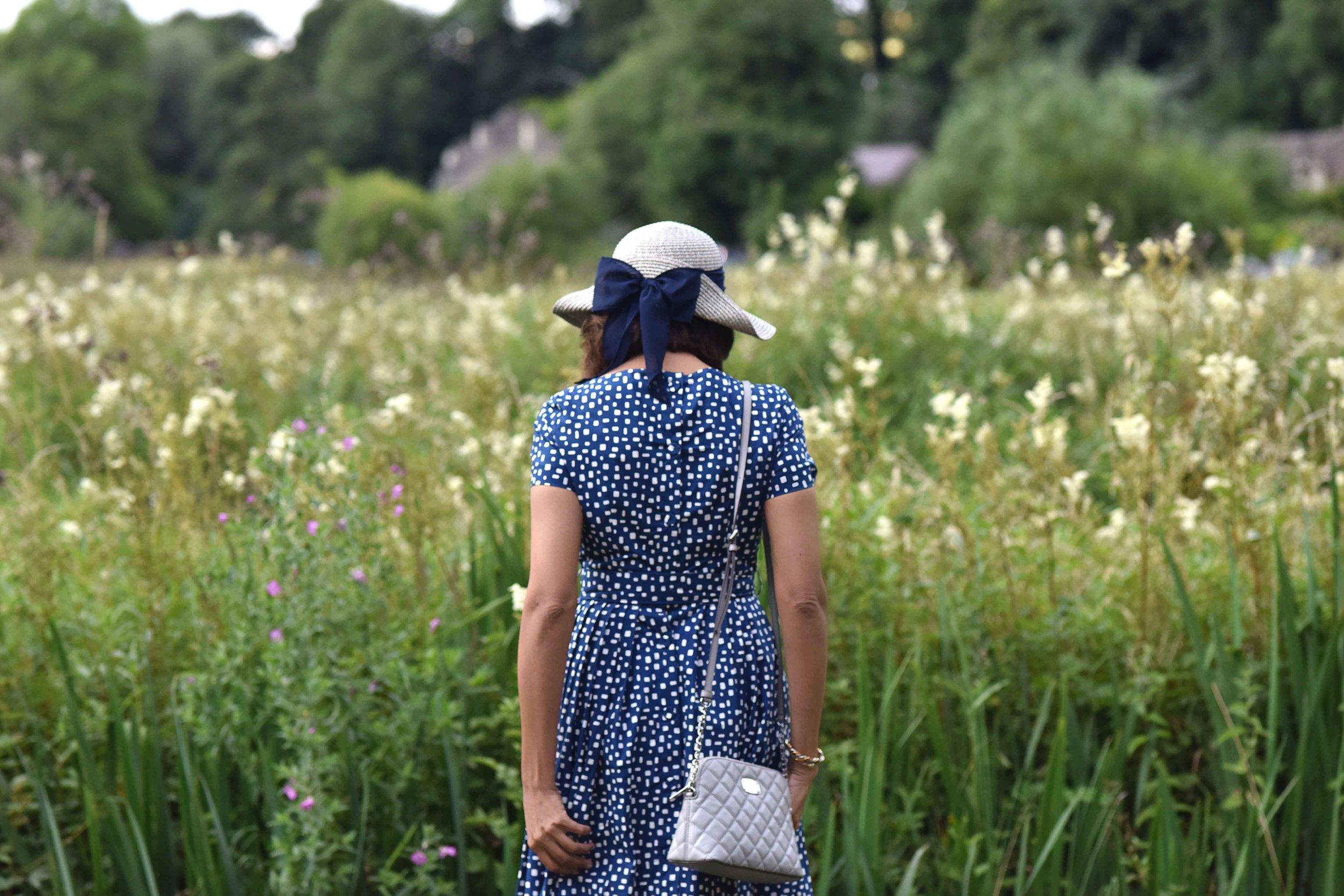 In a Prada dress, Michael Kors bag, Arlington Fields, Bibury, Cotswold, England. Image©sourcingstyle.com