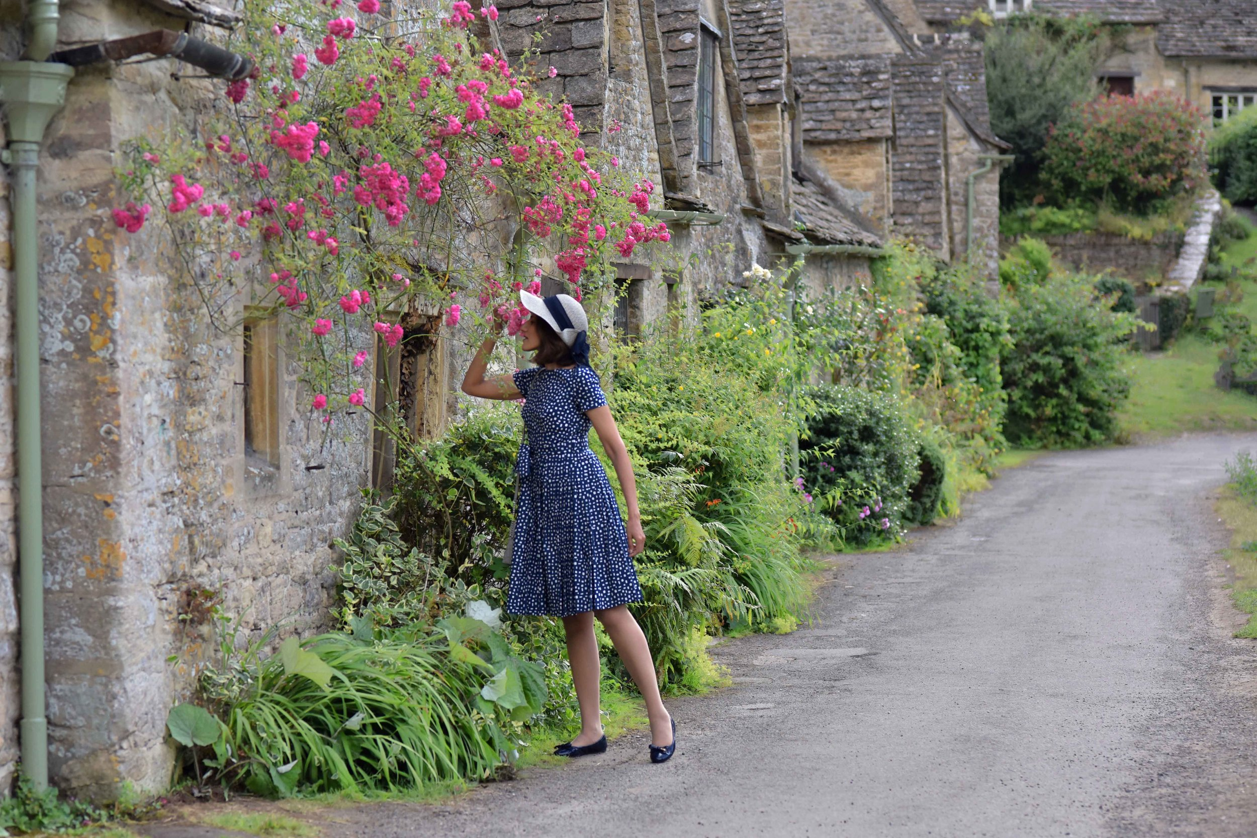 Prada dress, Prada ballet flats, Cotswold stone cottages, Arlington Row, Bibury, Cotswold, England. Image©sourcingstyle.com