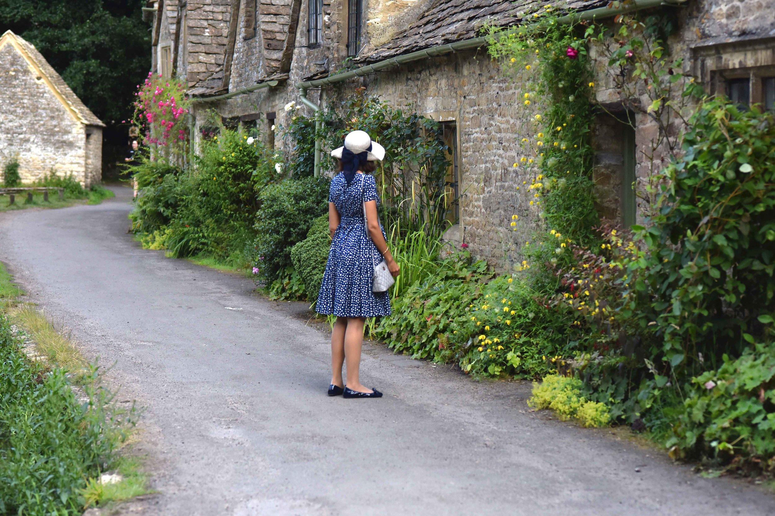 Prada dress, Prada ballet flats, Michael Kors bag, Cotswold stone cottages, Arlington Row, Bibury, Cotswold, England. Image©sourcingstyle.com