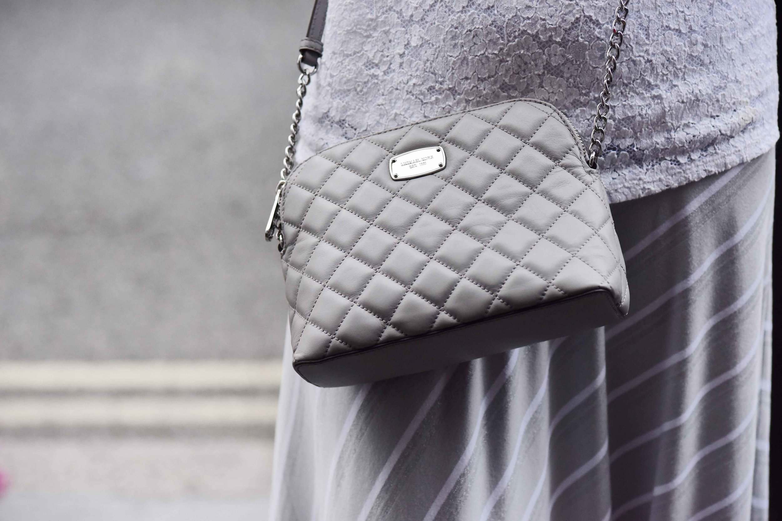 Summer street style, Michael Kors crossbody bag, Marks & Spencer white lace top, Chicos bias cut grey striped skirt. Image©sourcingstyle.com