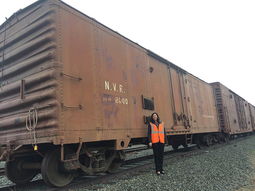 [Here is Kim Powers (former NV Wine Train employee and early supporter of the Quake Mosaic project) standing next to a sample disused rail car like the kind we plan to use for the mosaic substrate. ]