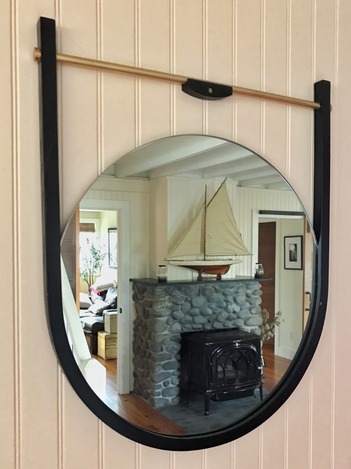 "Near the cottage entrance, the "" Moana mirror "" by O&G captures a view of the original stone fireplace surround which was fitted with a new wood-stove insert, new soapstone mantel, and new soapstone hearth as part of the KHS renovation."
