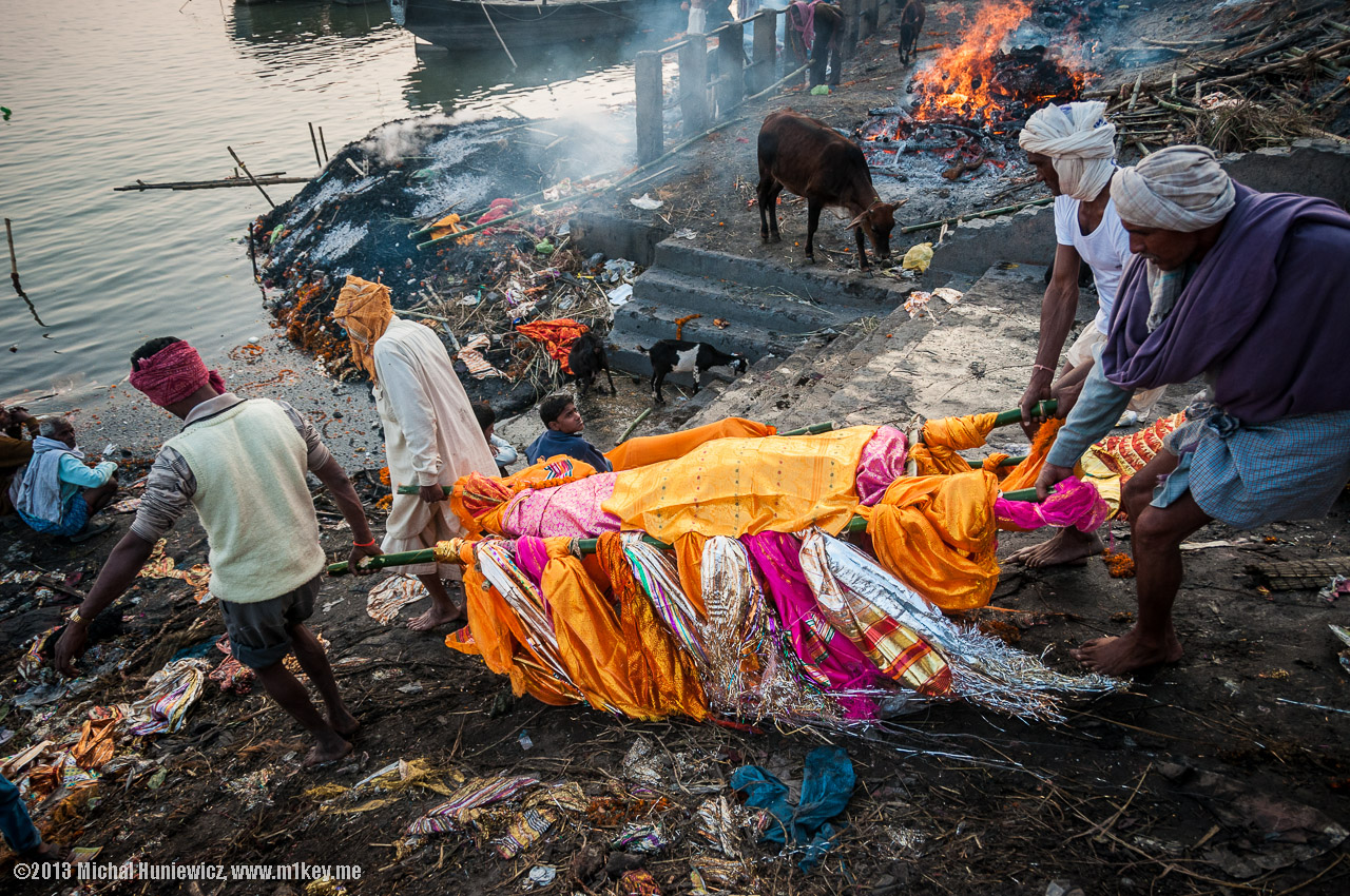 """You'll see bodies being transported throughout the city. It's a scene I will never forget...A body held over the heads of family members, mourning and chanting.All the bodies are kept in a few large buildings by the waters edge until it's time for the cremation to occur. Hindus believe that this is a """"rite of passage"""". It prepares their life for the afterworld.  *Picture taken from google images because you're not suppose to take pictures while observing the cremations."""