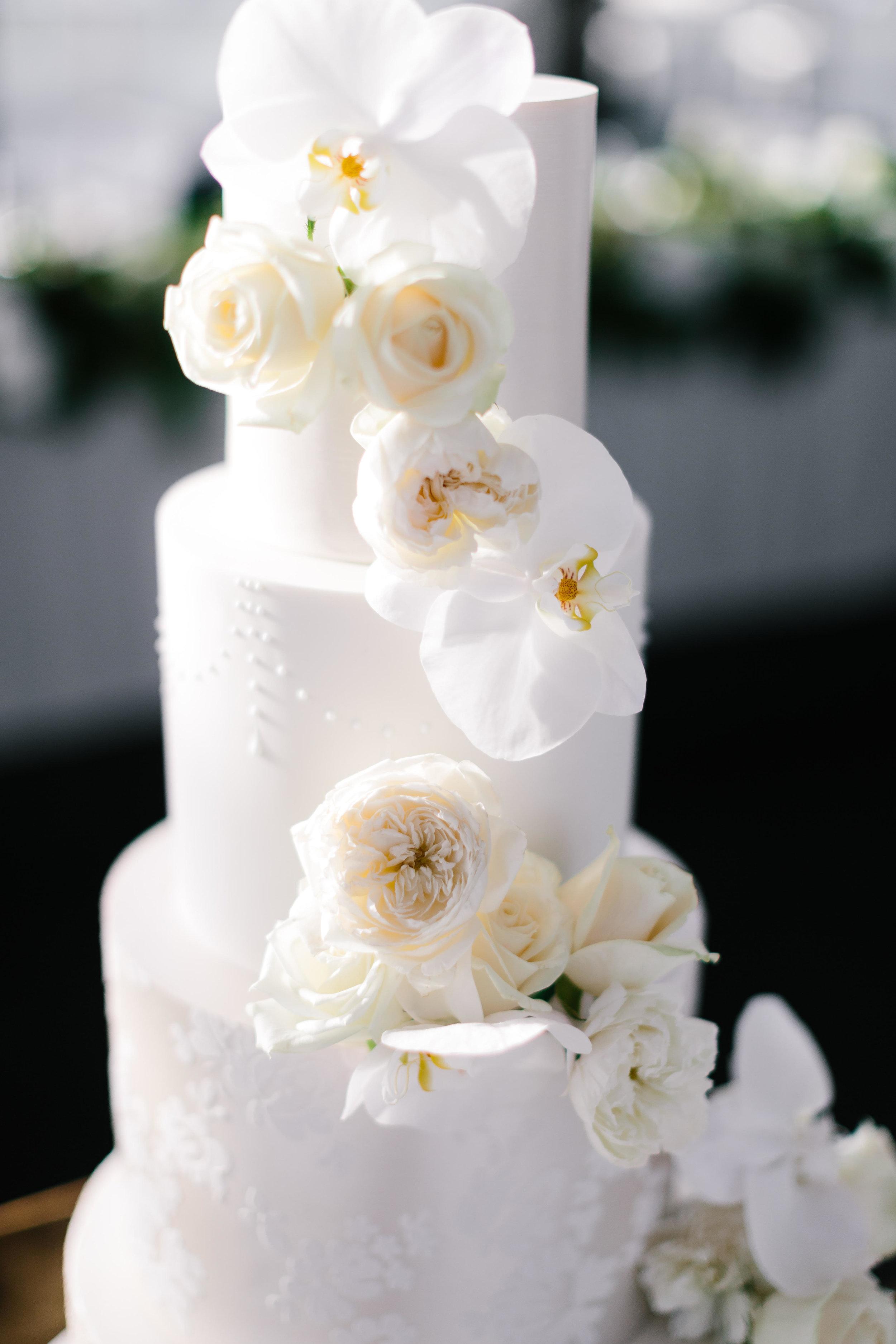 Wedding cake adorned with stunning fresh roses & phalaeonopsis orchids