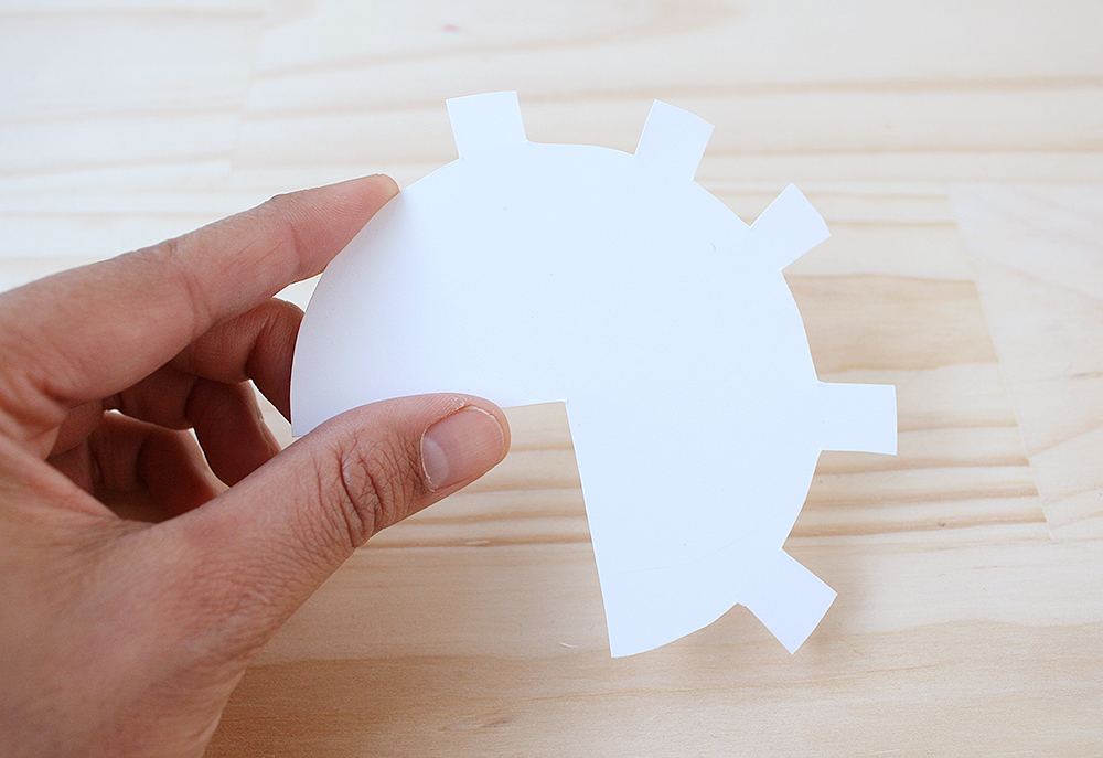 Step 3   Draw a circle onto the white card, approximately 8.5cm in diameter. Find the centre of this circle, then mark out a quarter wedge. Then mark out a few tabs around the circle and cut the whole thing out.