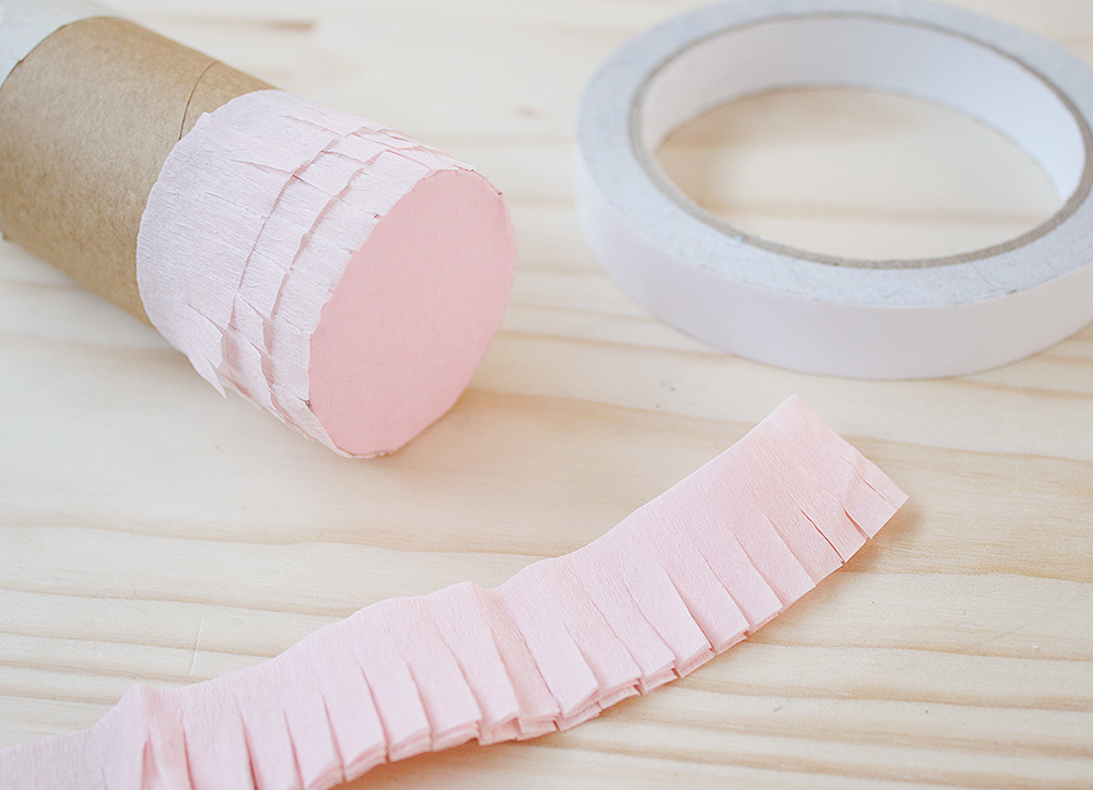 Step 7   Starting at the base, stick three rows of pink fringe onto the roll using double-sided tape.