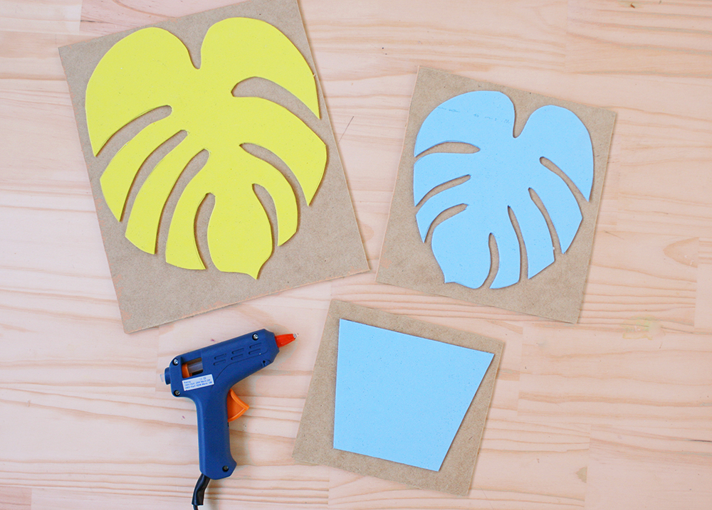 Step 1    To create stamps for printing, cut one planter pot and two different-sized tropical leaves from the craft foam (we used a monstera leaf shape). We made our shapes large enough to comfortably fill the pink card when stamped. Use the hot glue gun to stick each foam shape onto a separate piece of wood.
