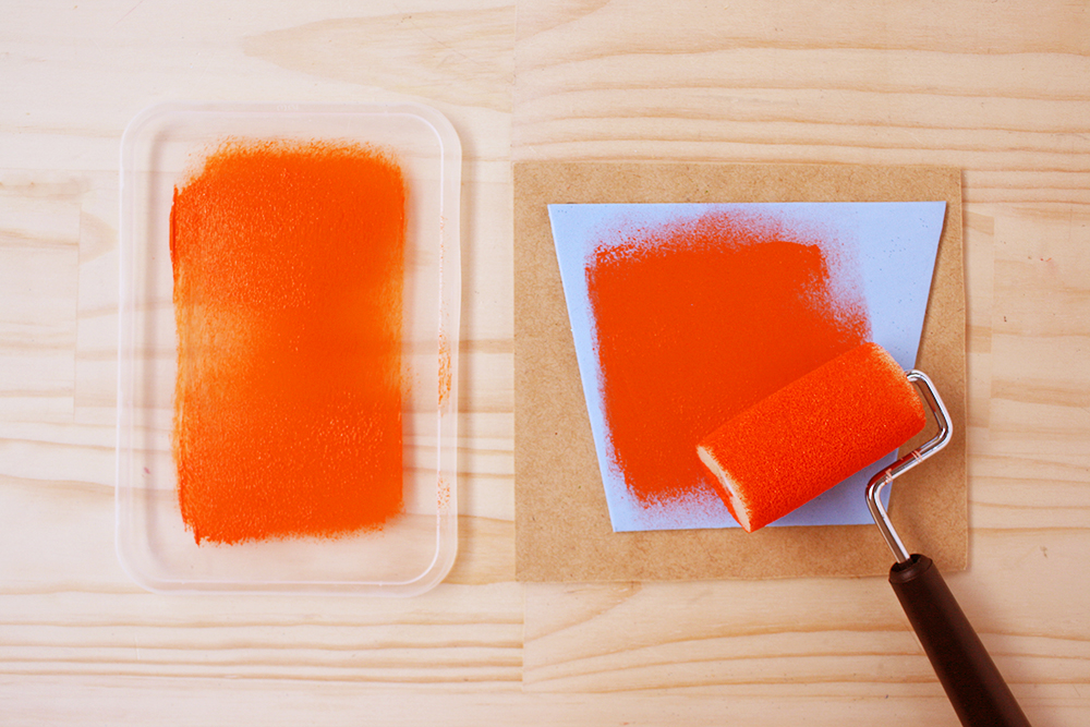 Step 2   Roll some orange paint evenly onto the sponge roller (use a scrap container lid or plate as a palette), then transfer to the pot plant stamp, ensuring that you get an even coverage of paint over the foam.