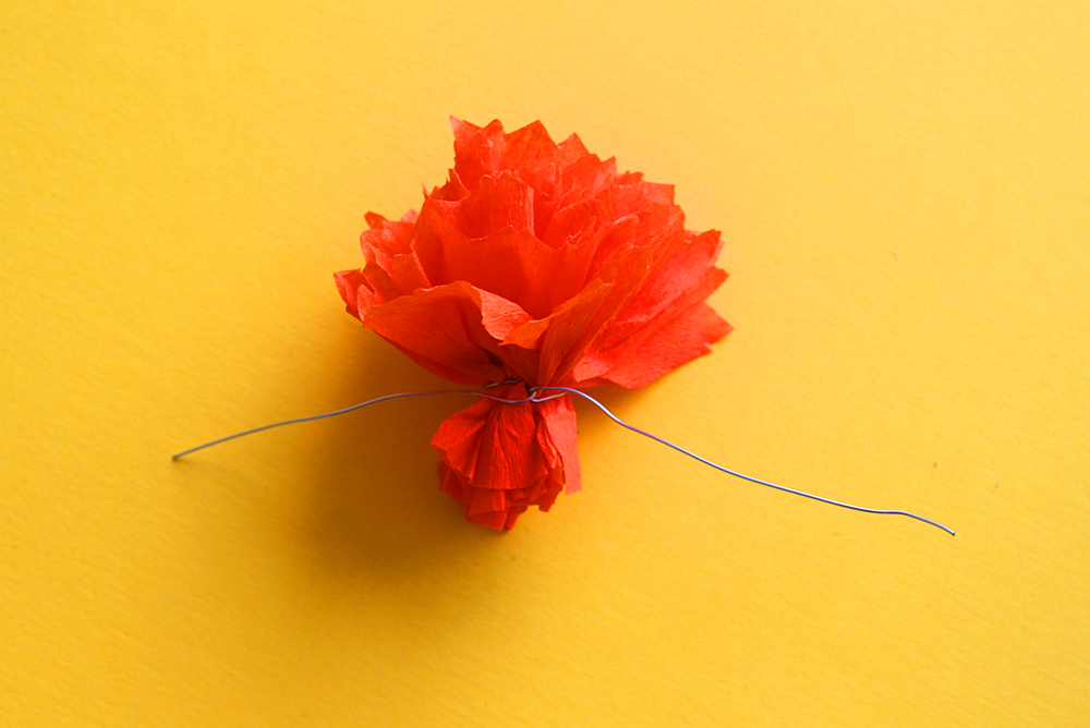 Step 3   Cut a 10cm piece of wire. When the flower is the size you want it at (more wrapping will make a bigger flower, less will make a smaller flower) wrap the wire tightly around the base of the bloom and twist to secure.