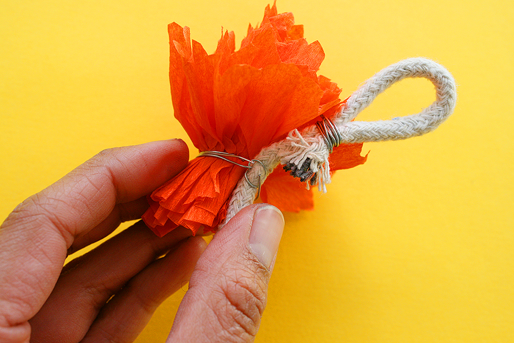 Step 14    To attach each flower, use the wrapped wire on the flower to secure it to the rope.