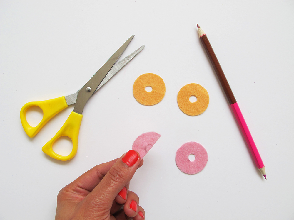 Step 3  To create the donut holes, fold each circle in half and draw a tiny semi-circle along the straight edge of each piece. Cut along this line and unfold.