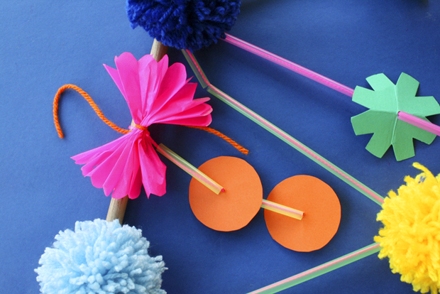 Step 7  Tie blue pom poms onto the dowel rod, at the points where the two larger components are knotted. Alternate with light blue and dark blue pom poms. Tie the pink bows to the dowel rod at the points where the orange circle strands are knotted.