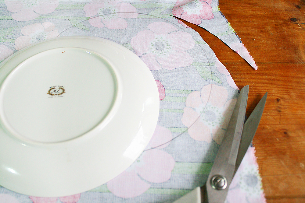 Step 1  Trace around the small plate onto the back of one piece of the fabric. Cut the shape out, leaving 0.5cm space around the traced line as you cut for your seam allowance.