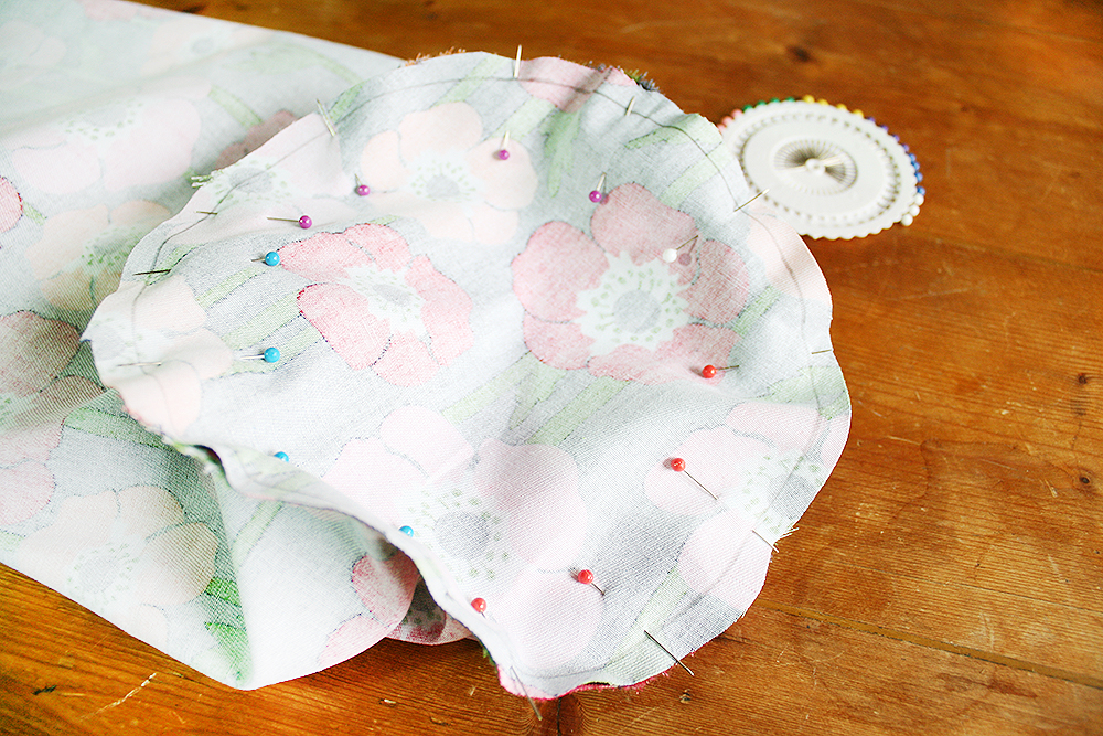 Step 5  With everything still inside-out, pin the circle to the bottom opening of the tube and carefully sew around it using the 0.5cm seam allowance, pulling out the pins as you go. Make little snips around the curve of the circle, making sure not to cut through your sewing. This helps create a neater circle shape.