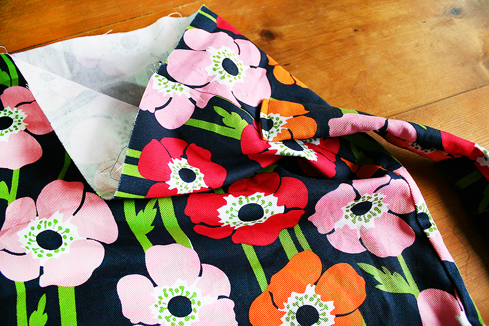 Step 6  Cut a thin strip of fabric approximately 8cm wide and 40cm long (it depends on how long you want your strap to be). Fold this in half with right sides facing in, and sew down the long edge using a 0.5cm seam allowance. Turn this inside-out. You could use a special turning tool for this, which is available at most craft stores. Otherwise, attach a paper clip to one end and work it bit-by-bit up through the tube to the other side. Fold each end over and sew it down to make a neat edge. Sew the strap onto the bag, approximately 6cm from the top and 2cm from the bottom.