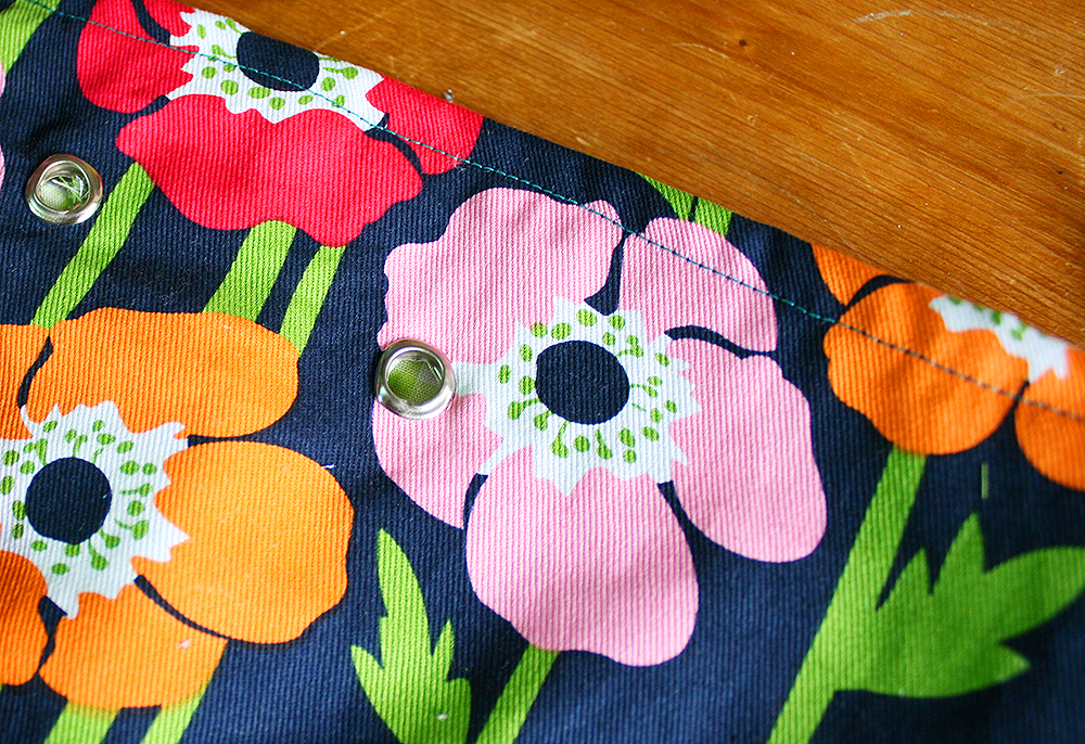 Step 9  Affix seven eyelets around the bag (through both layers), approximately 4cm down from the open end, using the instructions on the packet. Using the small sharp-nosed scissors, cut any excess fabric out from the centre of each eyelet.