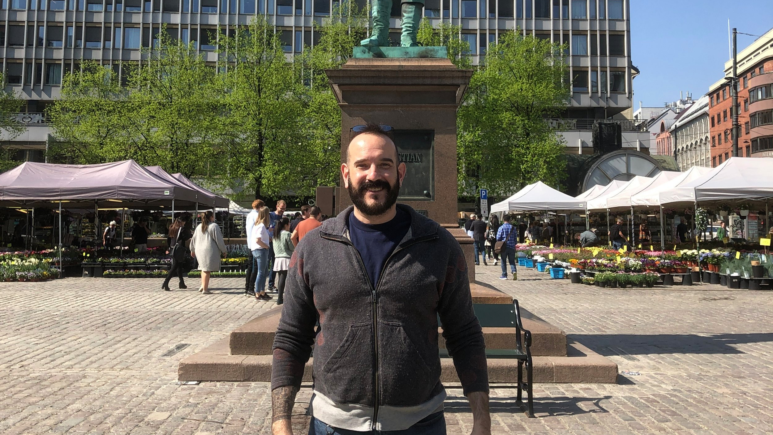 Mathew posing in front of a statue of Christian IV, at Oslo City Center.