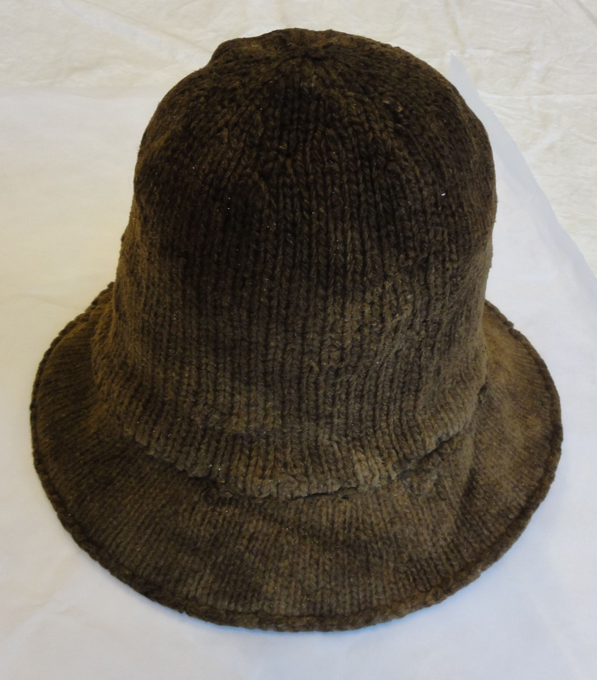 This image shows the unique bind-off edge at the outer perimeter of the brim. It is not a purl-ridge turned edge as so many reenactors use. Also, it is clear that the brim and the crown are knit in two different gauges.
