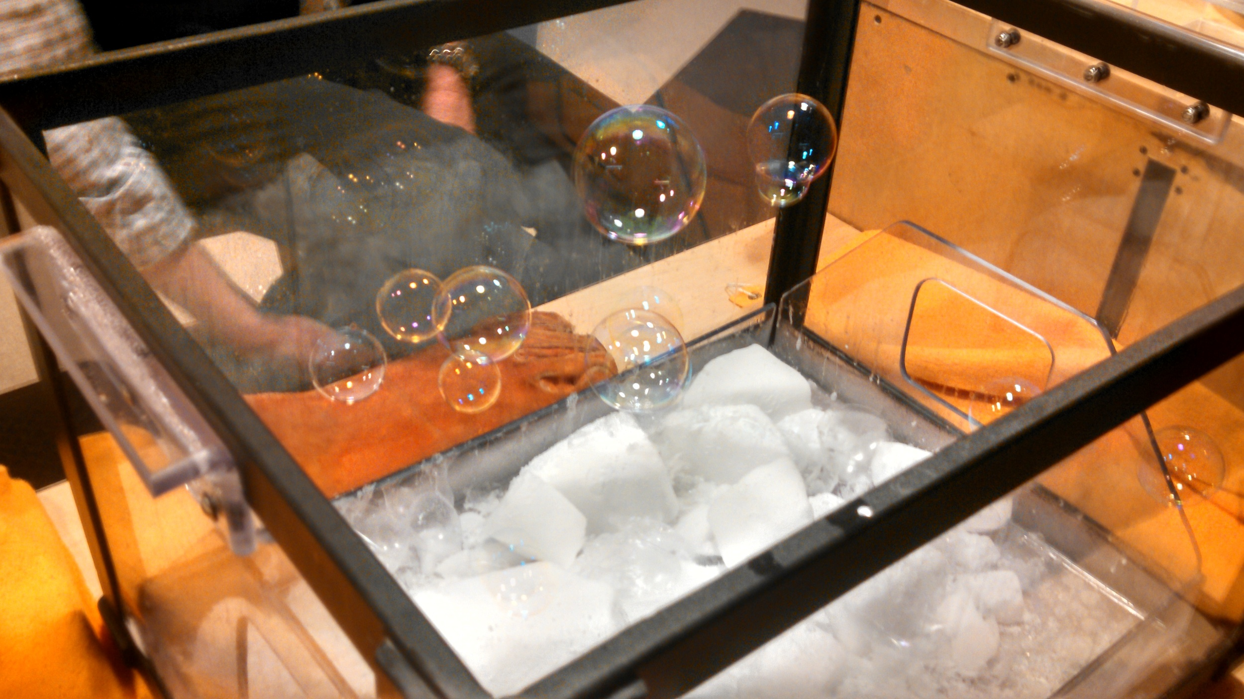 Bubbles hover in a container of dry ice!