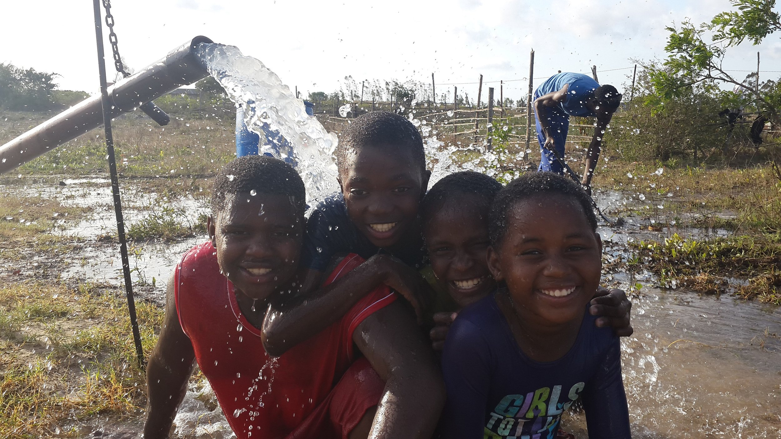 Children enjoy the novelty of pumped groundwater for the first time
