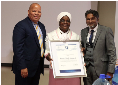 Ms Rebecca Pfarelo Ramugondo (centre) receiving an award for her outstanding contribution, commitment and support to communities struggling with water challenges from Mr Errol Gradwell (CEO EWSETA) (left), and Mr Dhesigen Naidoo (WRC) (right).