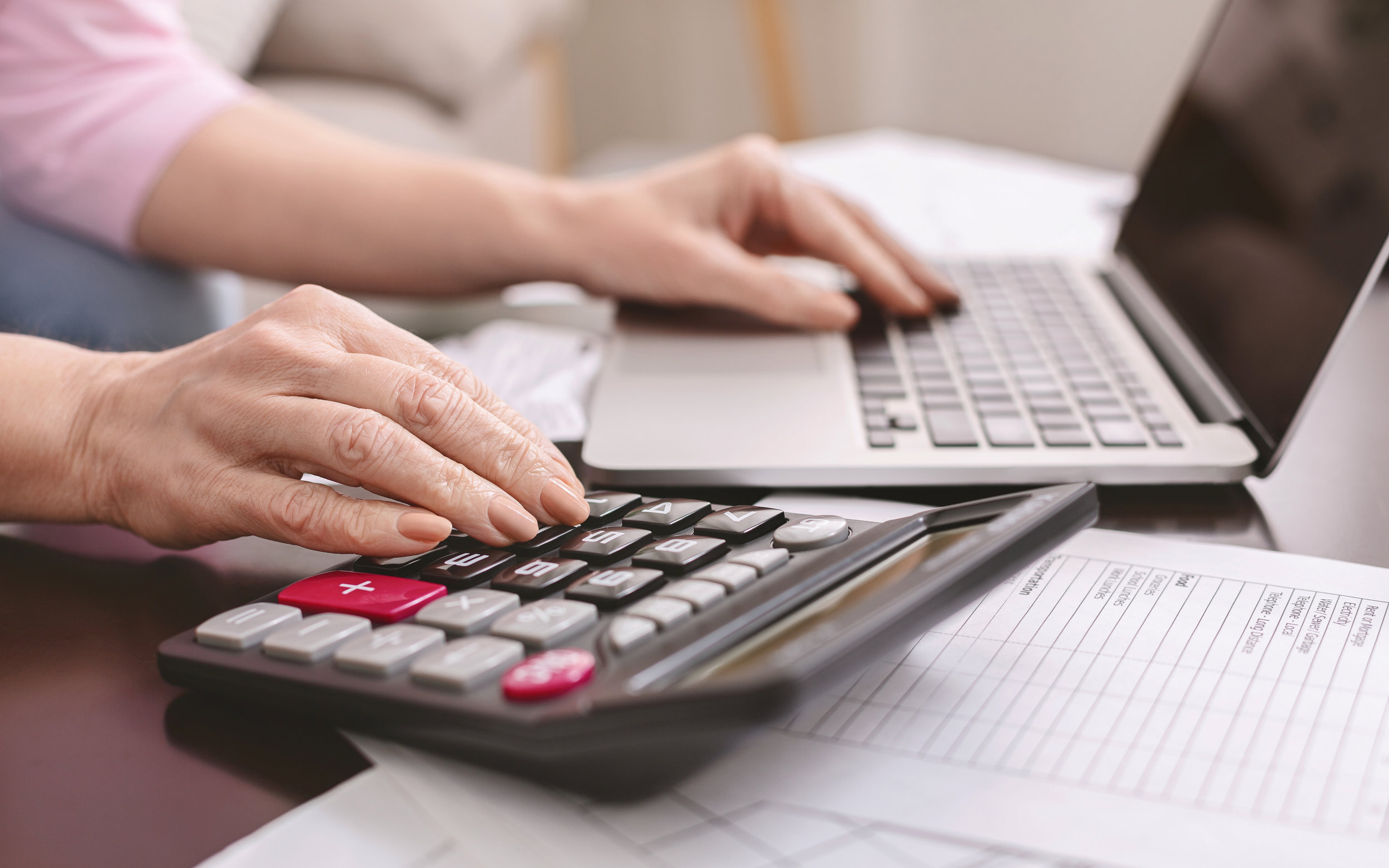 senior-woman-with-calculator-counting-dollar-QTZBNJ2.JPG