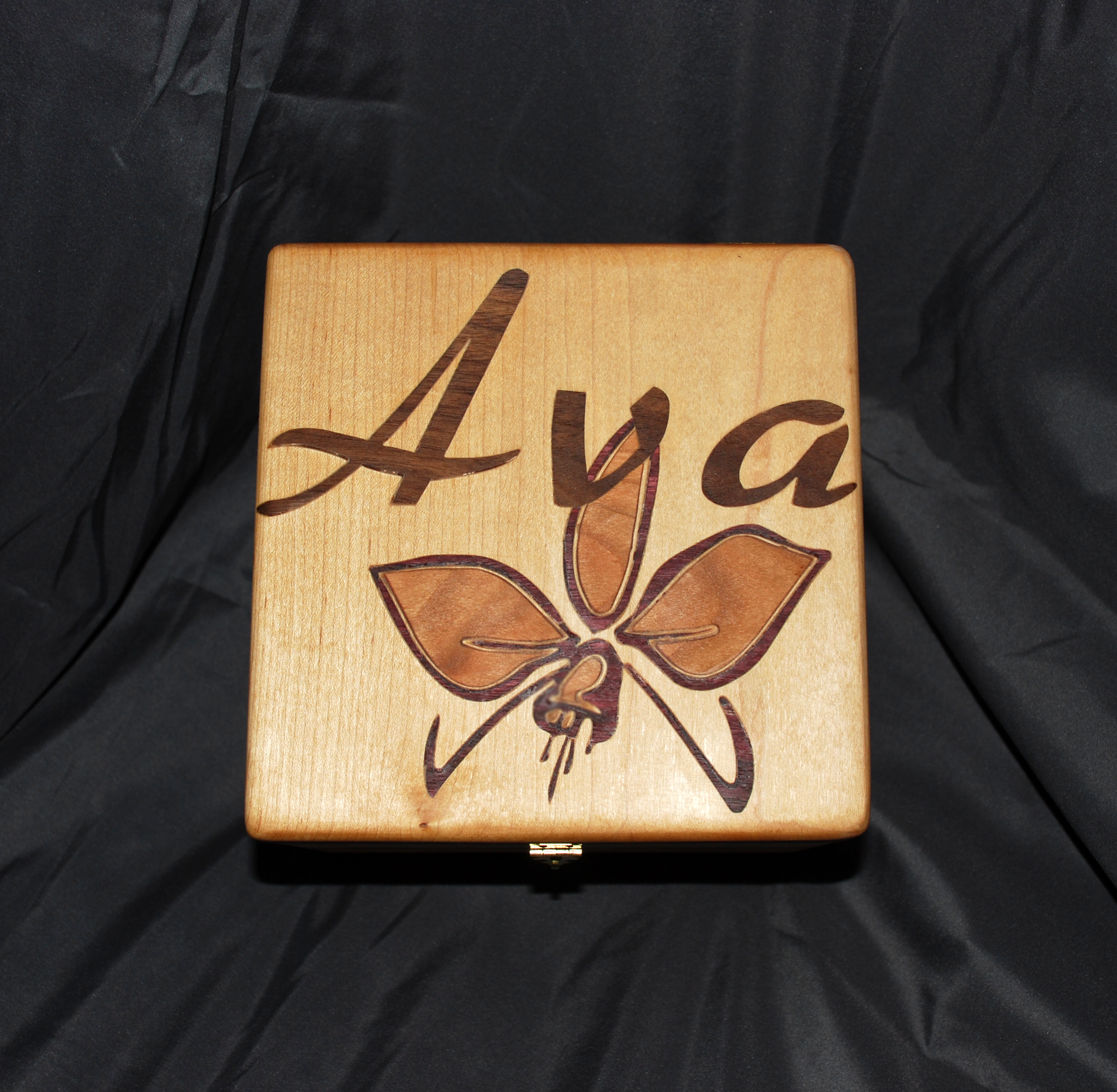 This is an example of a hardwood inlay.  The background wood is White Maple, the lettering is Mahogany, and the orchid uses a combination of Purple Heart (edges) and Cherry (leaves)