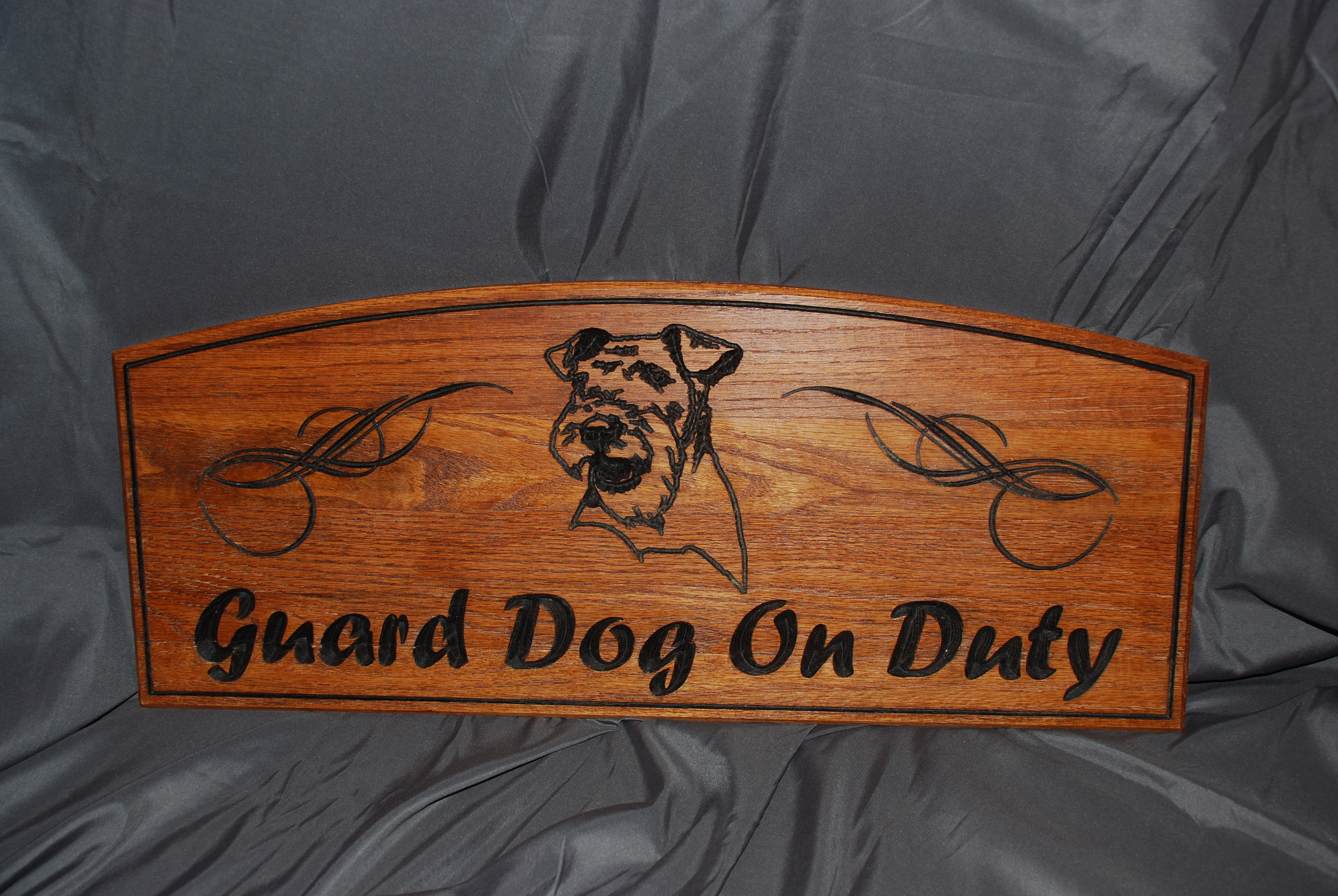 This sign was created using Red Oak stained with a Golden Mahogany finish. The images and lettering were V-carved and then stained a dark brown.