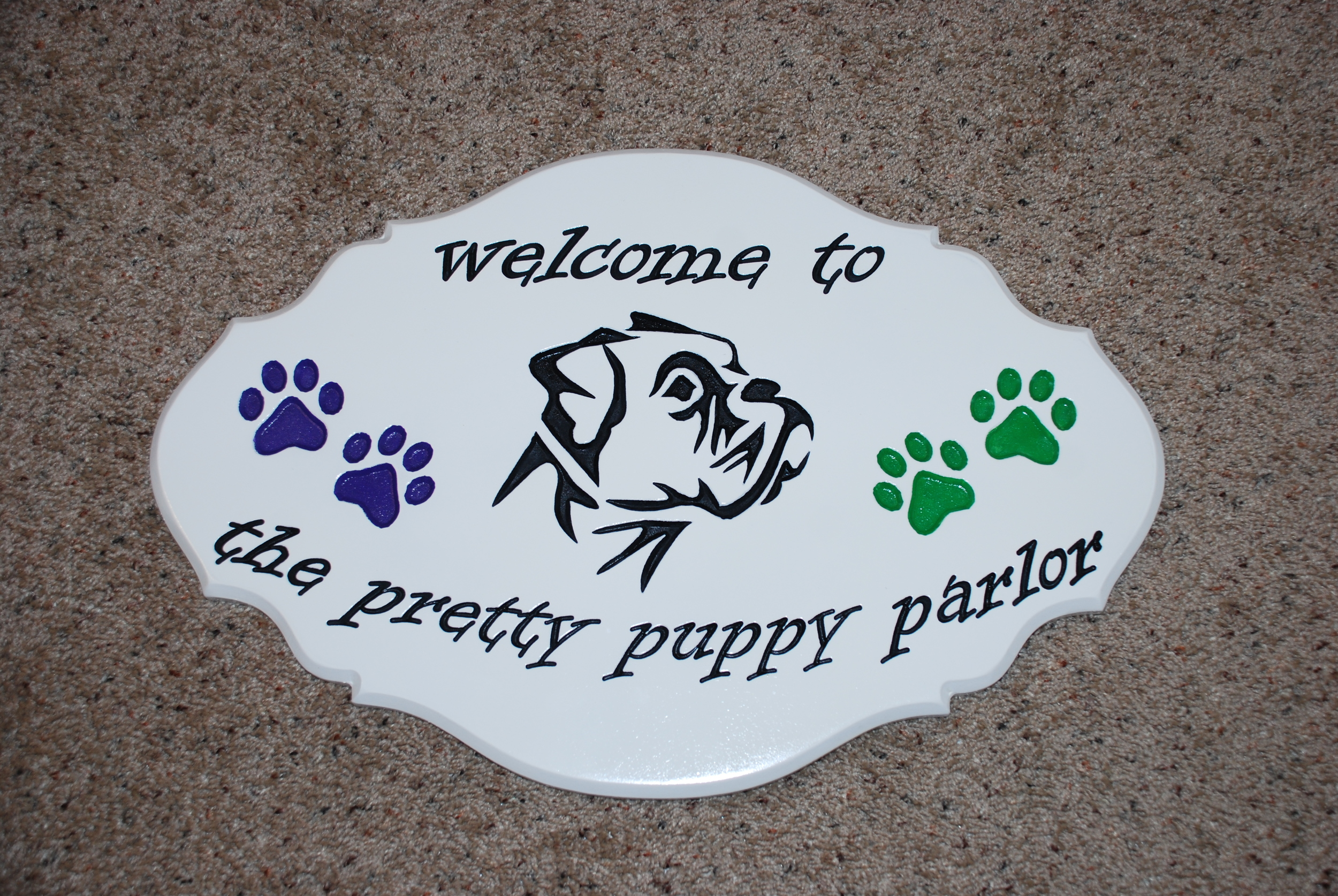 This sign was cut out of MDF (Medium Density Fiberboard). It was painted a gloss white, and the lettering and images were V-carved and then hand painted.
