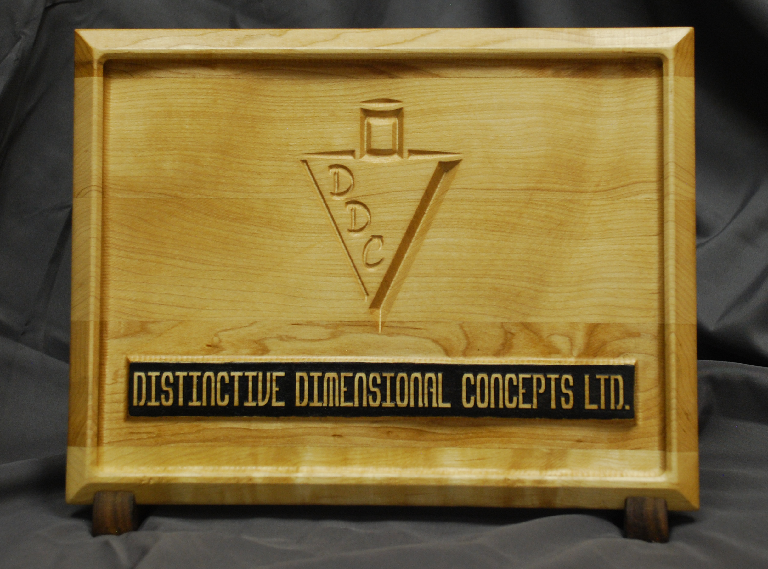 Created as a promotional piece, this sign was created using a combination of techniques. Starting with a 'blank' of laminated maple, the 'wavy' background was carved using a 3D relief. The DDC logo was V-carved into the background, and the company name was created using the Pocketing technique.