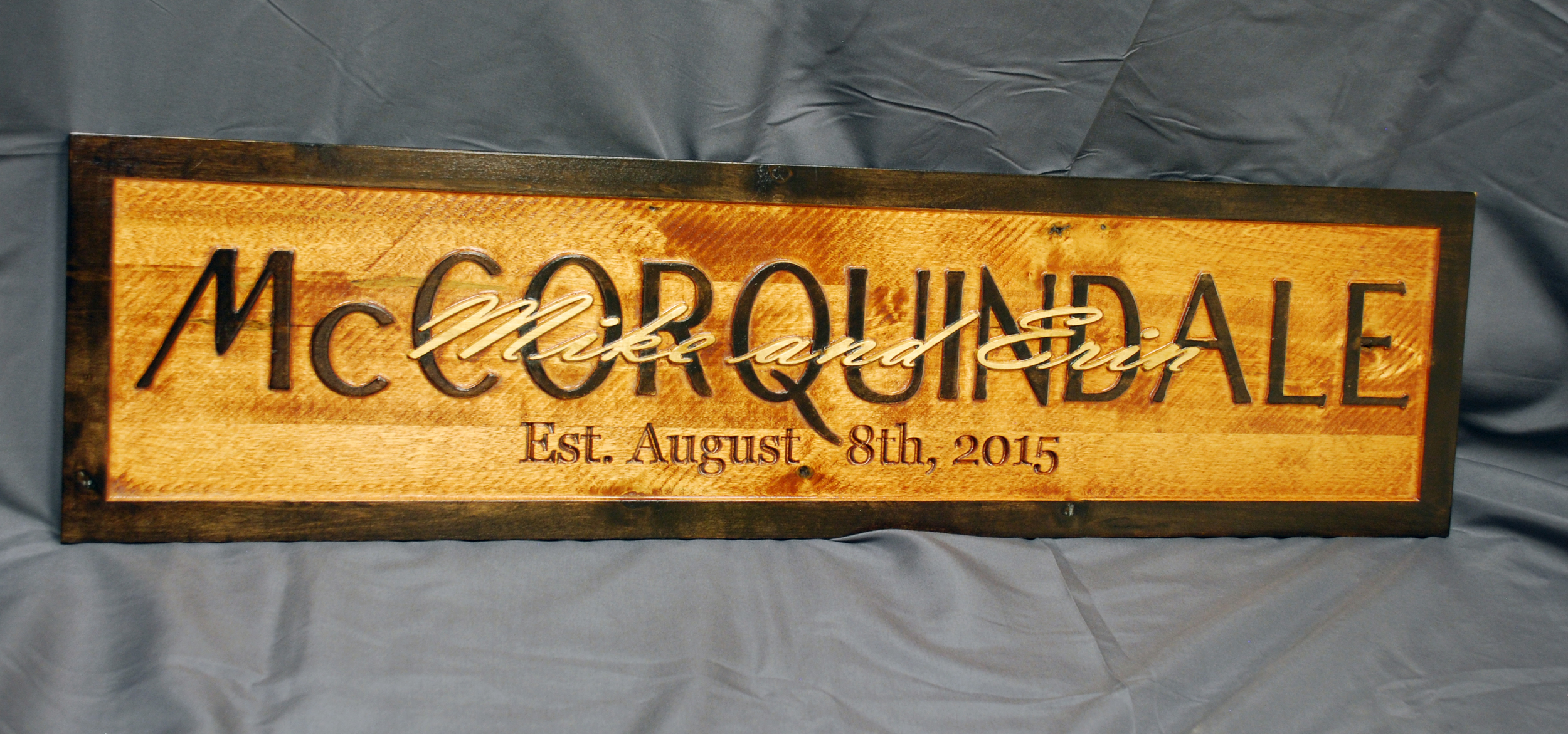 This wedding gift style sign is often referred to as a 'stacked text' sign. Starting with a slab of laminated birch, the lettering was cut out using the pocketing technique. The date lettering was cut using the V-carve technique. After the sign was completed, it was finished using a combination of colored stains applied by hand.