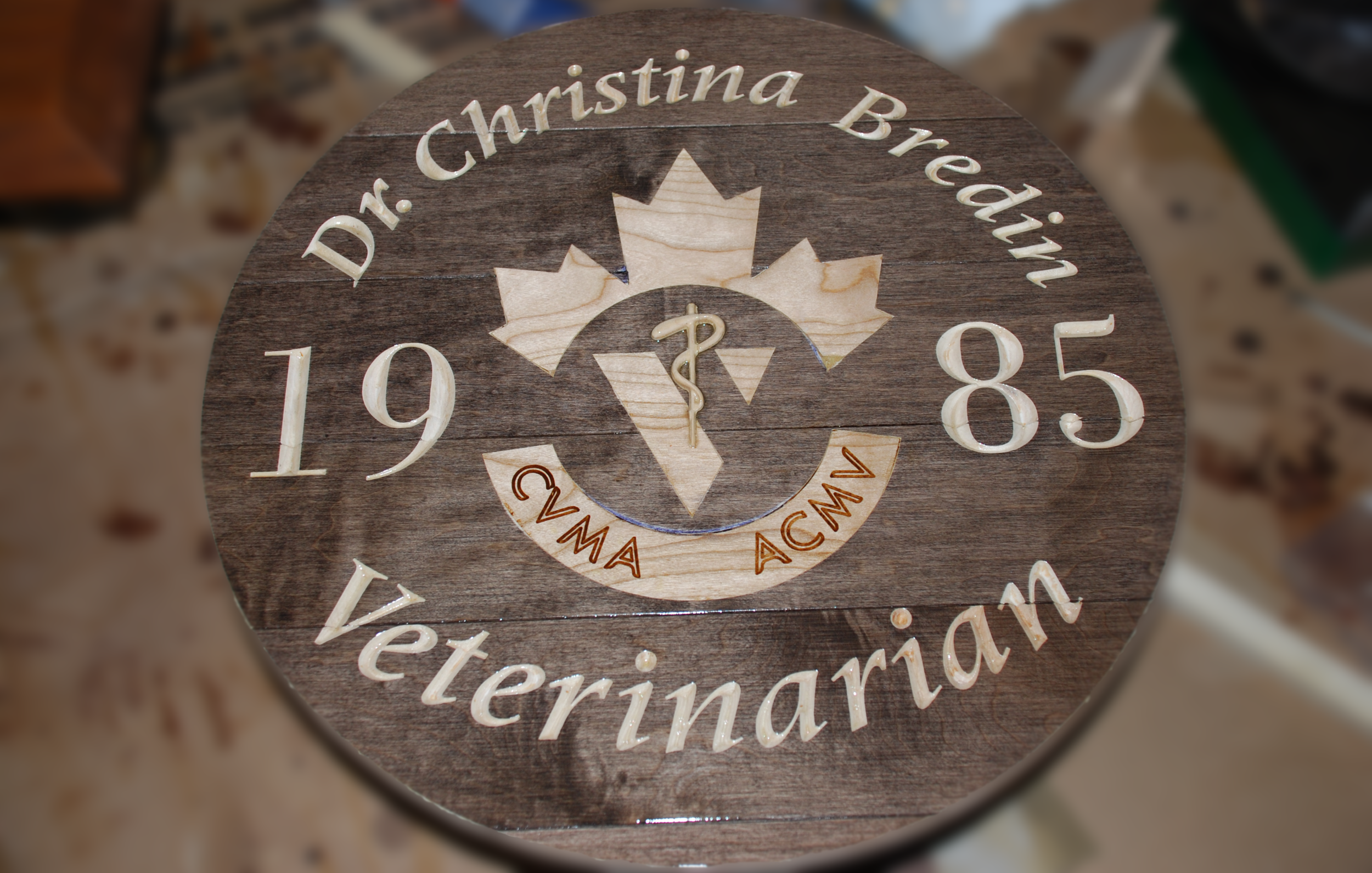 This sign was created using a laminated slab of pre-finished maple flooring. It uses a combination of V-carve, Inlay, 3D Relief and Engraving techniques.